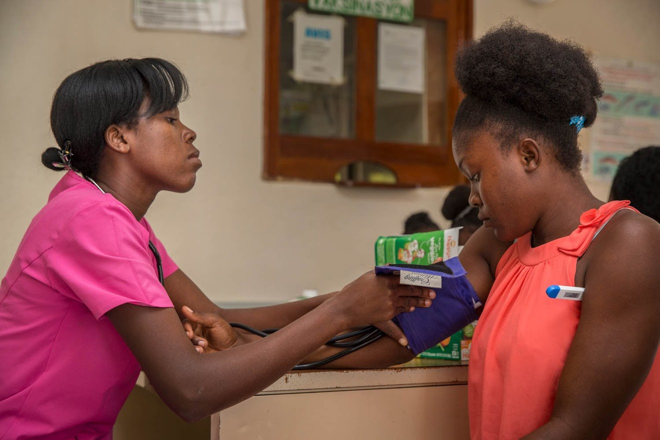 Imene Rigeur talks to a patient during at the Maison de Naissance clinic on Dec. 6, 2017. The clinic has a full range of facilities for expectant mothers, from consultation, delivery, and recovery rooms to a small medical lab and pharmacy. It is the only facility of its kind in Torbeck, Haiti. According to clinic director Rosena Baptiste, it's not unheard of for a patient to travel two to three days in order to reach the clinic. (Photo by Liam Storrings for Direct Relief)