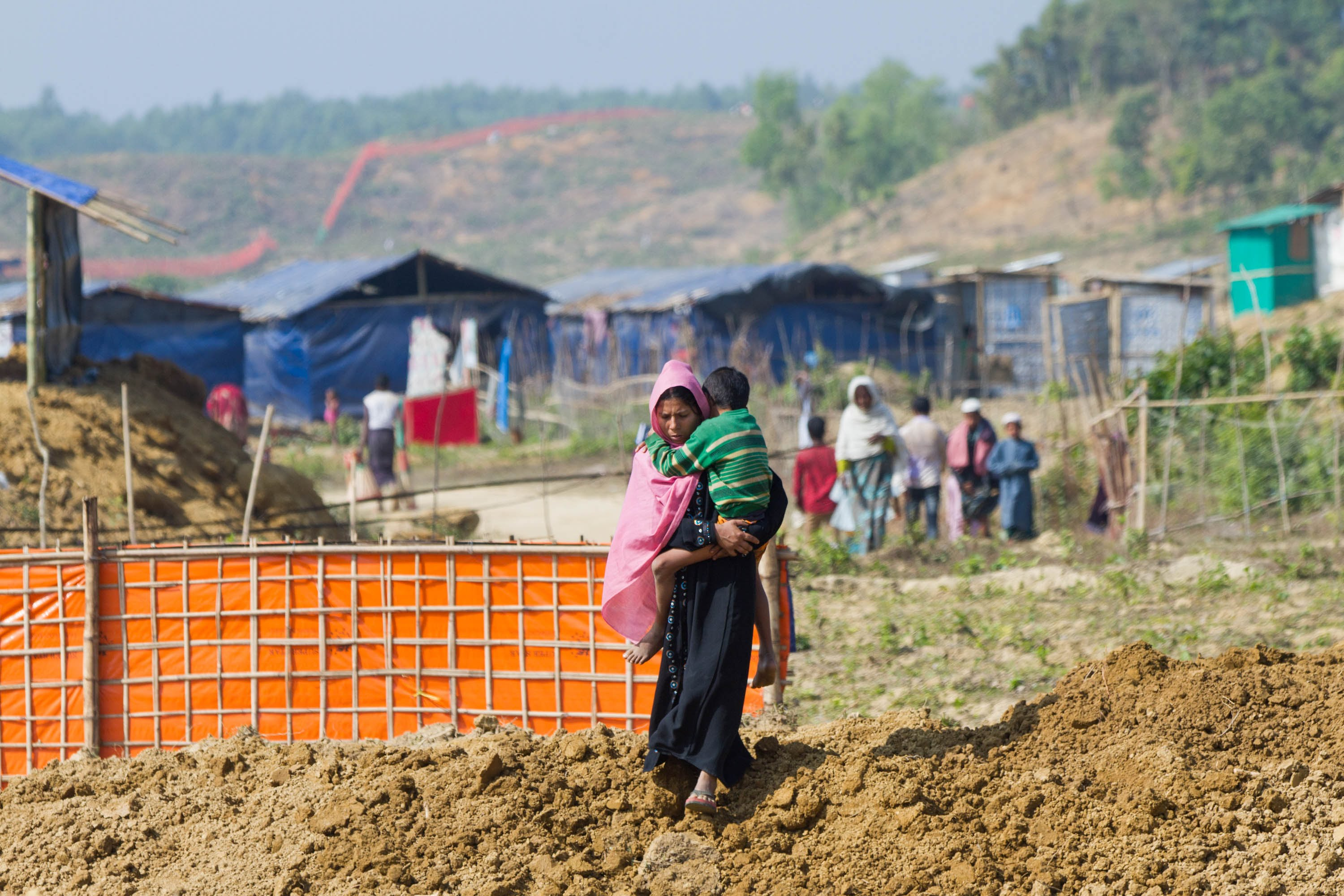 A Rohingya woman and her child walk towards Hope Field Hospital For Women in Madhuchara camp in Cox's Bazar, Bangladesh.  (Photo by Rajib Dhar for Direct Relief)