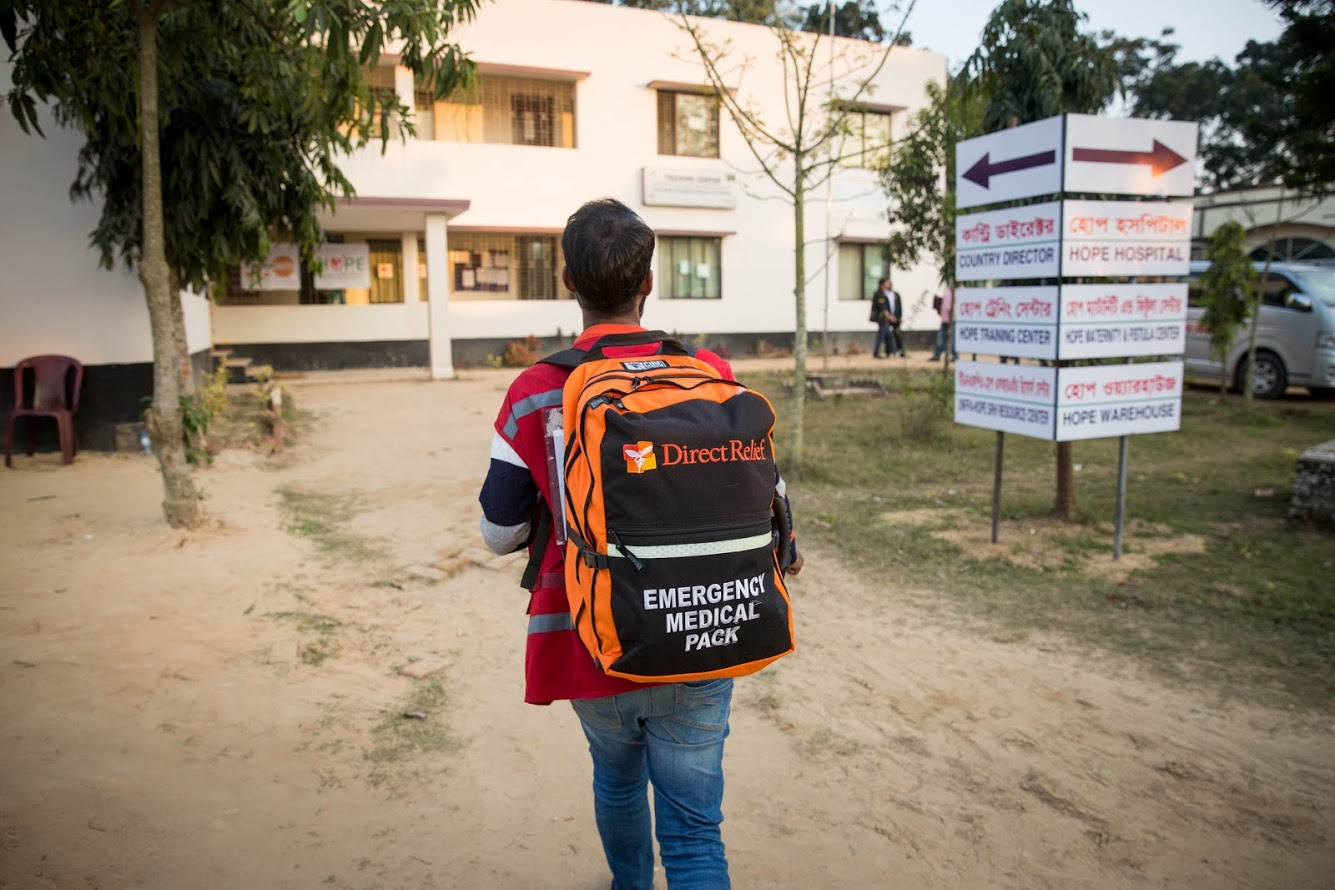 A volunteer carries a Direct Relief Emergency Medical Backpack outside of Hope Hospital in Cox's Bazar, Bangladesh. Direct Relief is supporting the hospital with medical aid as they work to establish field hospitals throughout the Rohingya settlements. (Photo by Rajib Dhar for Direct Relief)