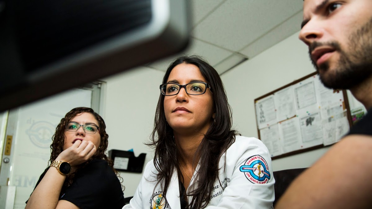 Radiologist Dr. Yania López Álvarez (center) reviews patient cases with residents Amanda Marrero González and Manuel Betancourt Robles at the Medical Center of Puerto Rico in San Juan, P.R., on May 10, 2018. Dr. López, Director of the Imaging Center of the University of Puerto Rico School of Medicine, returned to her homeland last year to work with the island's population, leaving behind generous job offers on the mainland. Doctors who work in Puerto Rico must do more with less, with budget restrictions and infrastructure still in disrepair from Hurricane Maria. (Photo by Erika P. Rodriguez for Direct Relief)