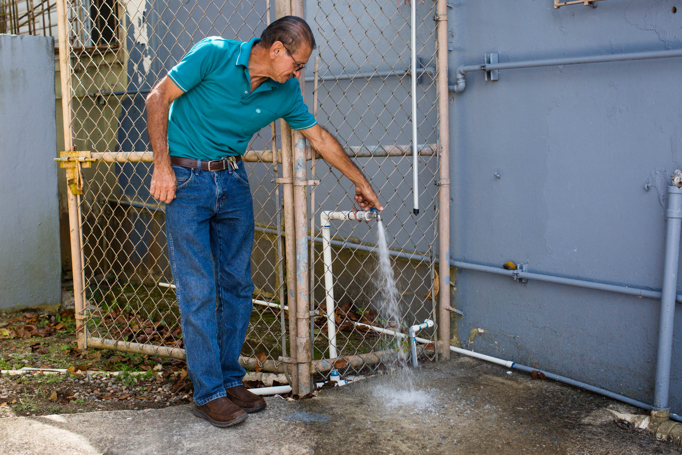 Miguel Morales, president of the community nonprofit Acción Comunitaria del Viví, Inc., checks the water pressure in the building before solar laundry services open in Barrio Vivi Arriba, Utuado, Puerto Rico, on May 26, 2018. Inside a former public school, the group, funded by Direct Relief, opened a free laundry service for the two nearby communities who have been without power for over eight months. The group, coordinated by Miguel Morales, serves as a community and aid center in the aftermath of Hurricane Maria. Many of the residents of the mountainous area are elderly and underprivileged. (Photo by Erika P. Rodríguez for Direct Relief)
