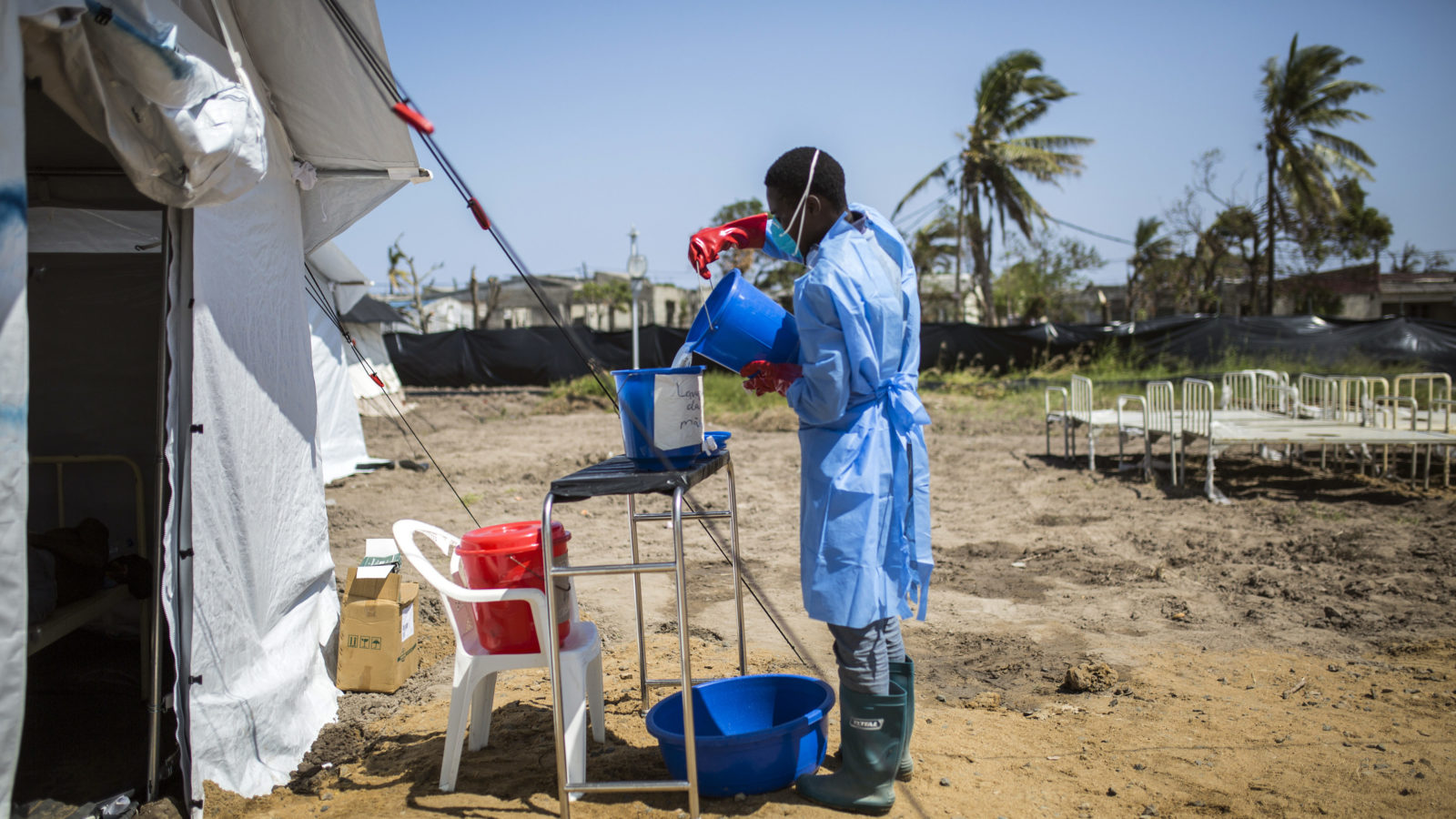 A medical worker fills a bucket with clean water outside an emergency treatment tent at the Macurungo Urban Health Center in Beira, Mozambique, on Friday, March 29, 2019. Cyclone Idai hit the Mozambican coast earlier this month, devastating the port city of Beira and killing at least 700 people in Mozambique, Zimbabwe and Malawi. Cyclone Kenneth is dealing a second blow to the country. (Guillem Sartorio/Bloomberg via Getty Images