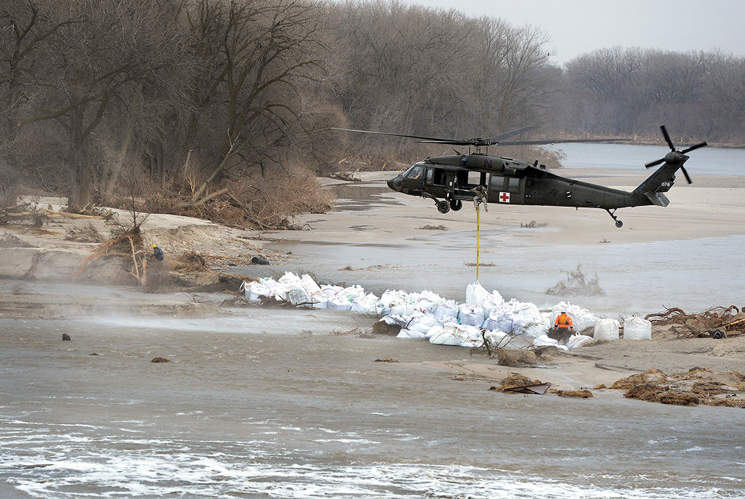 Sandbags are lowered to bolster a levee on the Loup River in Nebraska on March 23, 2019. Flooding has already inundated many parts of the Midwest, and another blizzard is expected this week, which could bring even more. (Photo courtesy of U.S. Air Force)