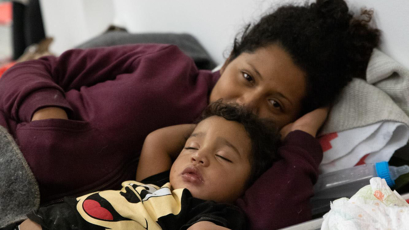 A child and mother rest on a cot at a San Diego shelter where local groups are providing essential services, including health care. Families seeking asylum spend one or two days at the shelter before traveling to join their sponsors. (Photo courtesy of Jewish Family Service of San Diego)