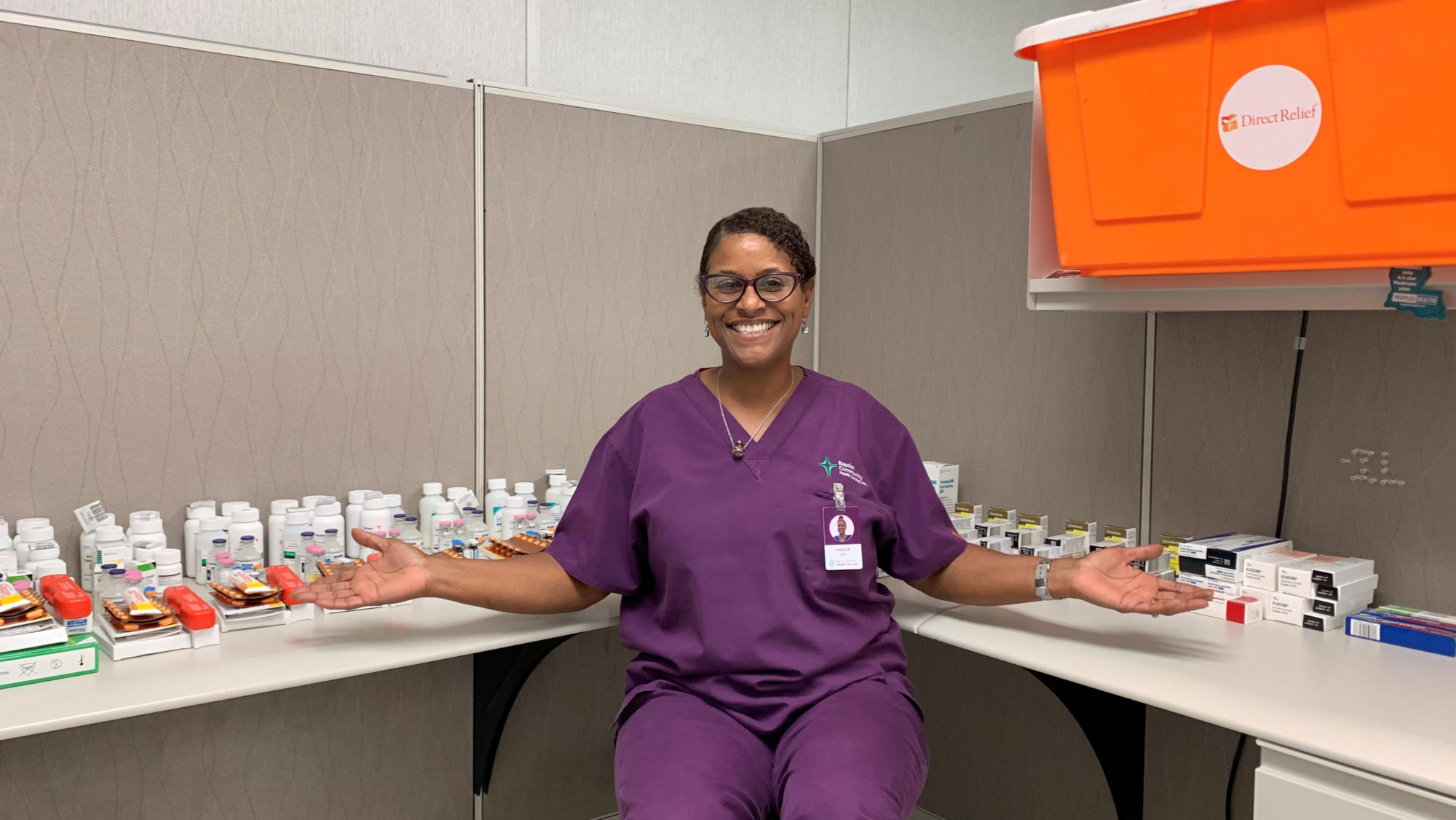 A staff member at Baptist Community Health Services shows off the sorted contents of a Direct Relief Hurricane Prep Pack. (Photo courtesy of Baptist Community Health Services)