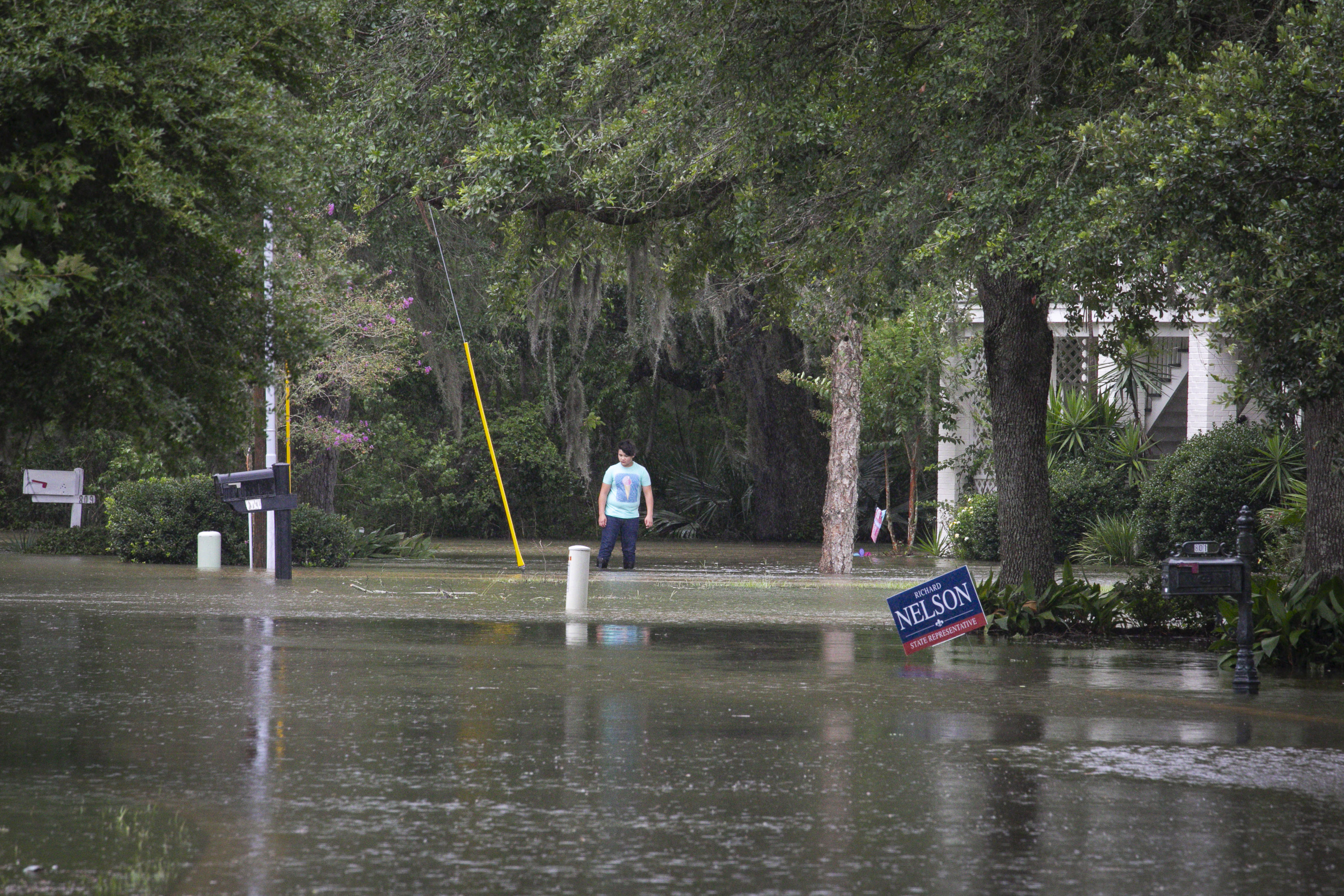 A resident stands in flood water outside a home near Lake Pontchartrain, after Tropical Storm Barry makes landfall in Lewisburg, Louisiana U.S., on Friday, July 13, 2019. Barry is threatening to bring life-threatening floods after making landfall in Louisiana on Saturday, as the tropical storm lashes the state with as much as two feet of rain. (Photo by Nicole Craine/Bloomberg via Getty Images)