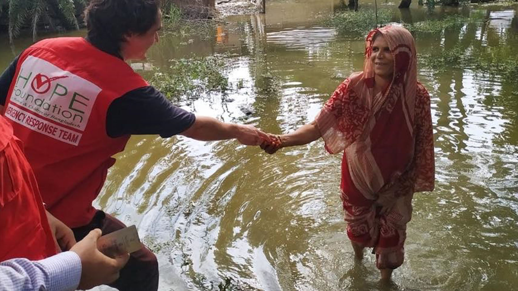 An emergency response worker from HOPE Hospital in Cox's Bazar, Bangladesh, helps a woman out of the water. Direct Relief is supporting the hospital with essential medicines, and will continue shipping requested medical aid to facilities responding to the flooding. (Photo courtesy of HOPE Foundation for Women and Children)