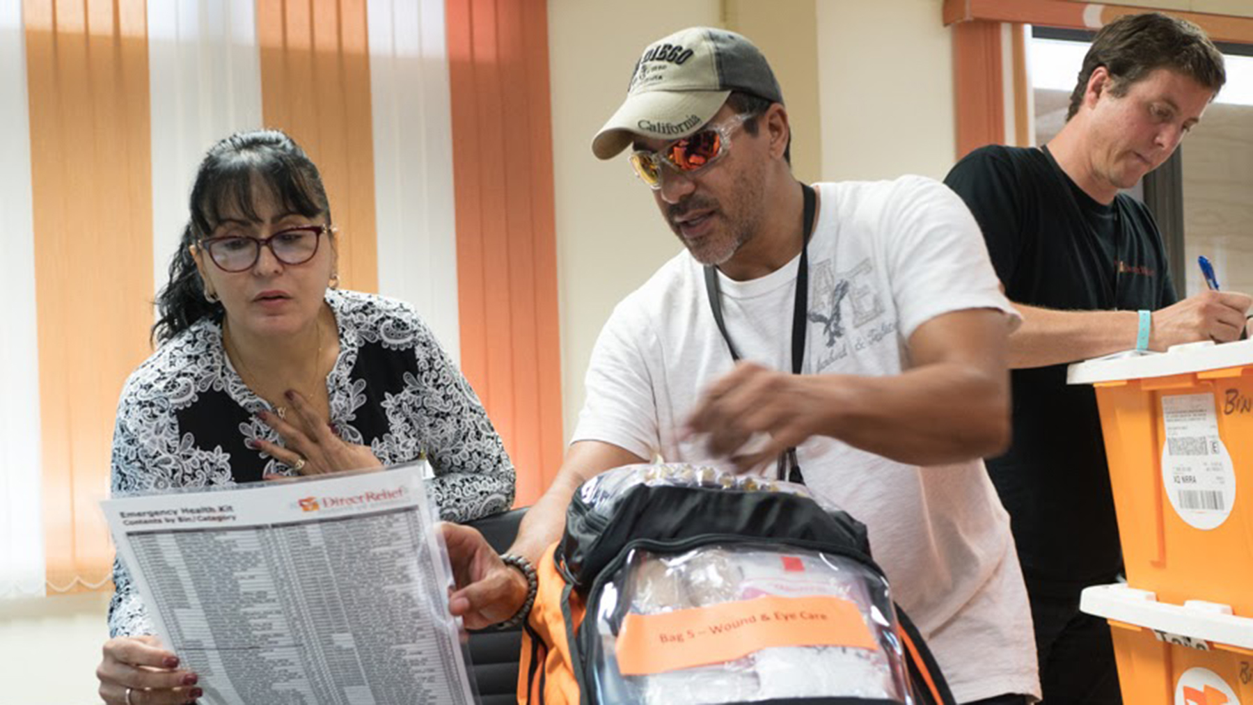 Dolores Morales, Executive Director of Migrant Health Center  listens to Daniel Ramos of the Asociacion de Salud Primaria de Puerto Rico as she receives medical supplies from Direct Relief following the path of Hurricane Maria through Puerto Rico on October 6, 2017 in Mayaguez. Morales said she feels the health center is better prepared for the next storm. (Photo by Angel Valentin for Direct Relief)