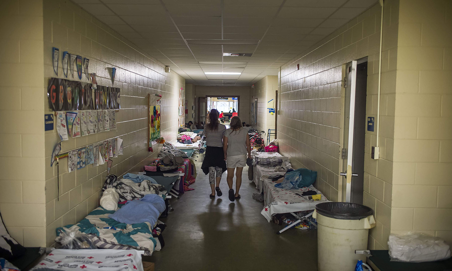 Evacuees walk the halls of a hurricane shelter in Panama City, Florida, in October, 2018, during Hurricane Michael. When people evacuate, they often forget medicines needed to manage chronic conditions, which can escalate into medical crisis. (Photo by Zack Wittman for Direct Relief)