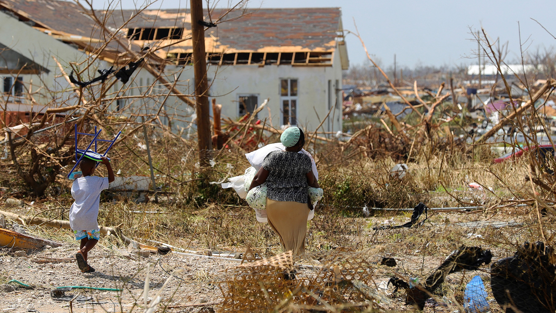 Residents of the island of Great Abaco, in the Bahamas, carry their possessions after Hurricane Dorian. (Photo courtesy of the UK Ministry of Defense)