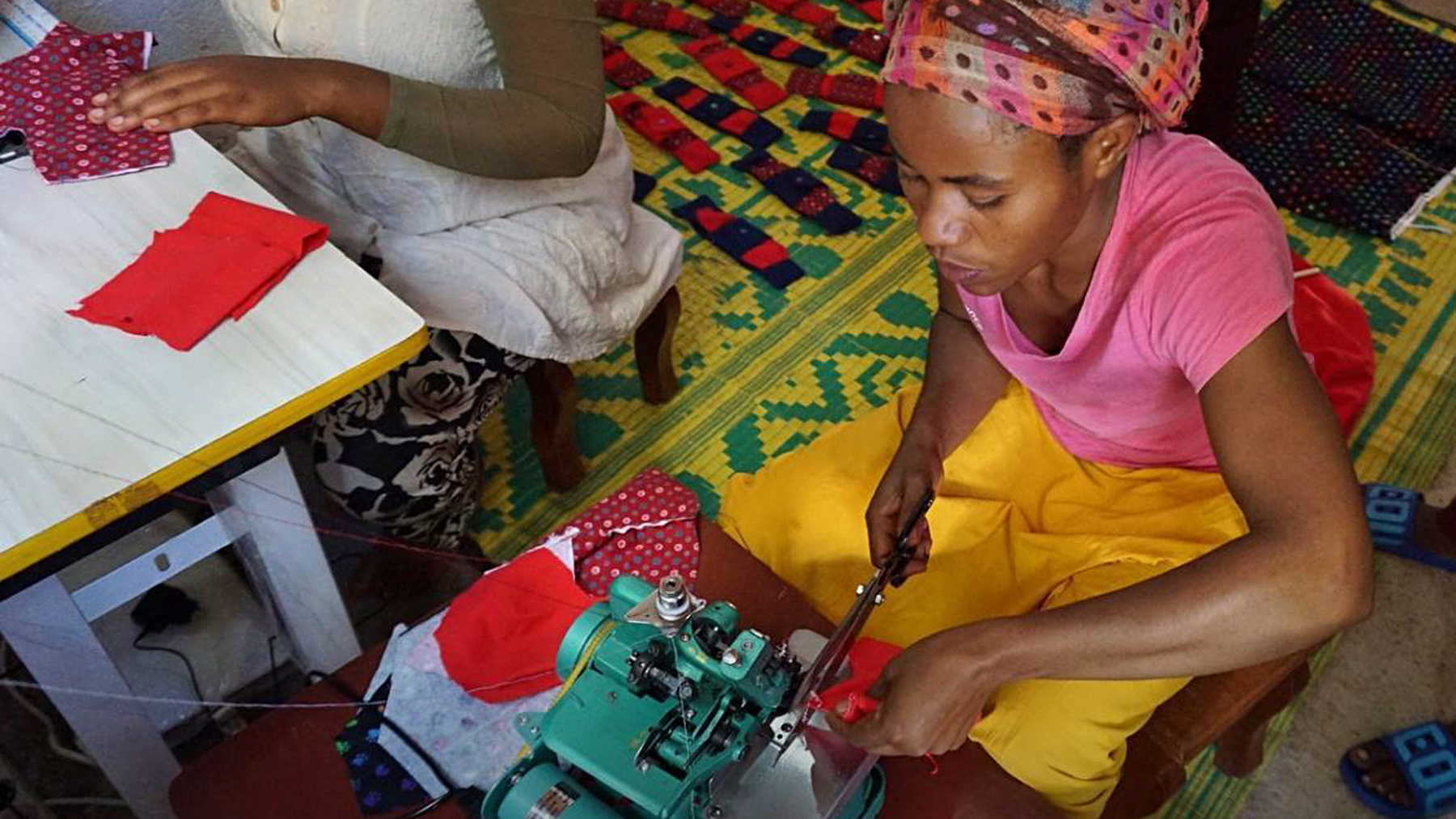A woman in Rwanda making Days for Girls kits at an orphanage, in coordination with World Dance for Humanity (Photo Courtesy of   Genevieve Feiner/ World Dance for Humanity)