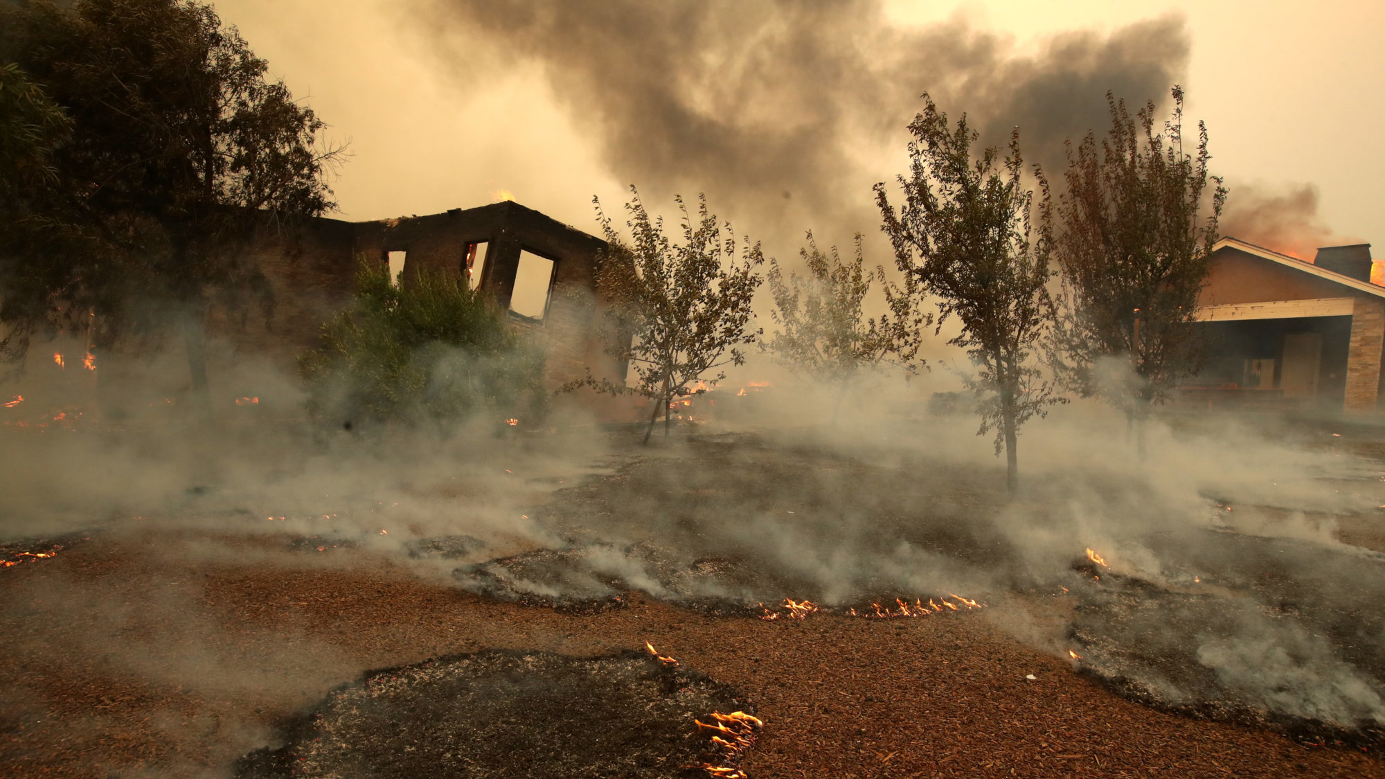 Small spot fires smolder near a destroyed structure in Geyserville, California after the Kincade Fire moved through the area. Fueled by high winds, the Kincade Fire has burned over 66,000 acres. (Photo by Justin Sullivan/Getty Images)