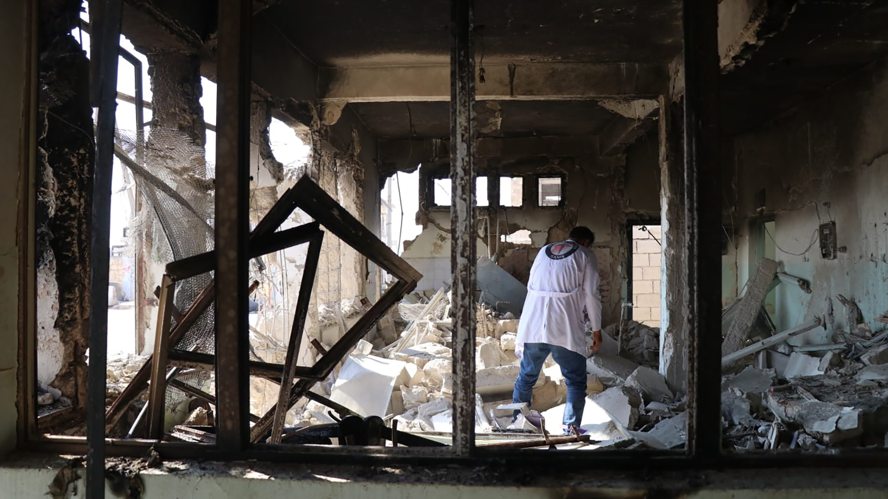 A Syrian American Medical Society health provider inspects a damaged building in northwestern Syria. The group is one of the few remaining groups working in the area, since many have left due to an escalation of aerial attacks since April 2019. (Photo courtesy of SAMS)