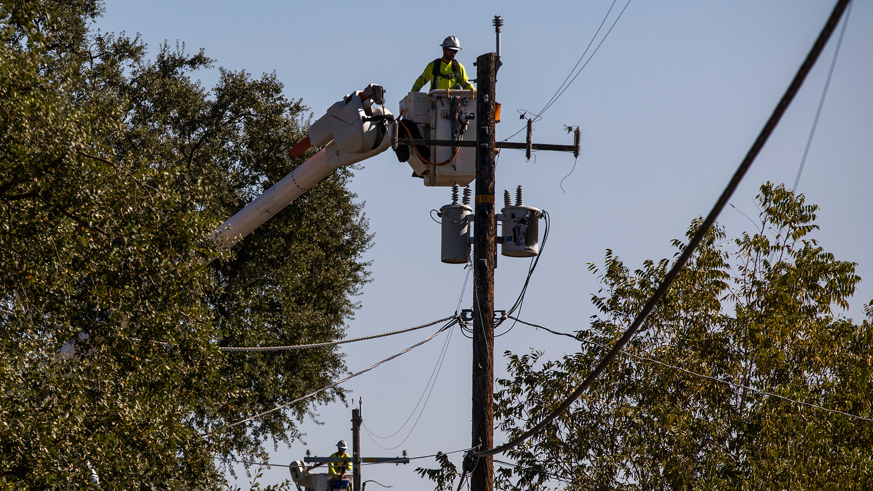 Contractors work on utility poles along Highway 128 near Geyserville, California, on October 31, 2019. Outages impacted much of the state this year, and health facilities were no exception. (Photo by Philip Pacheco / AFP via Getty Images)