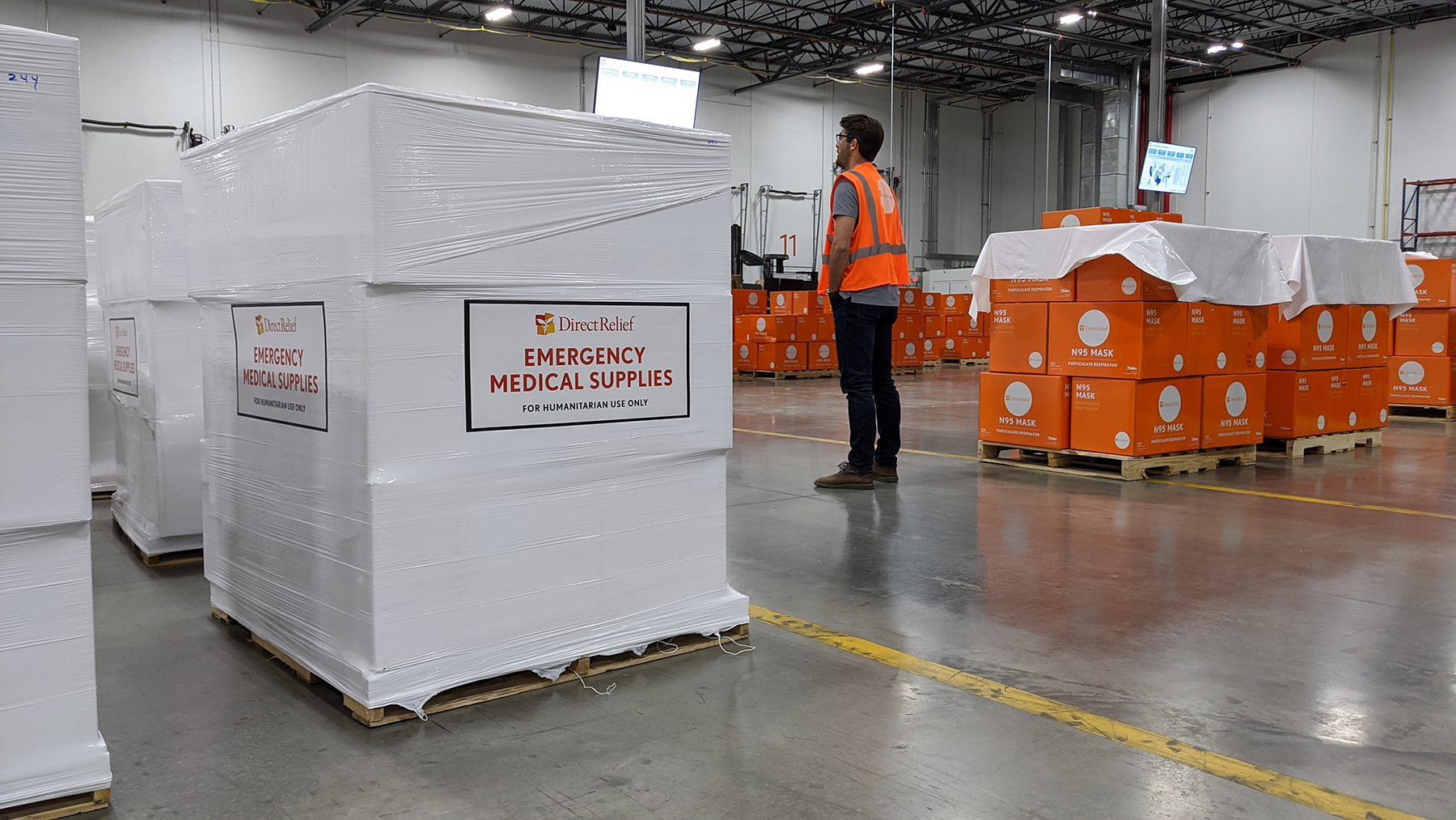 A Direct Relief staff member waits as pallets containing N95 masks are prepared for shipment to Australia. (Lara Cooper/Direct Relief)