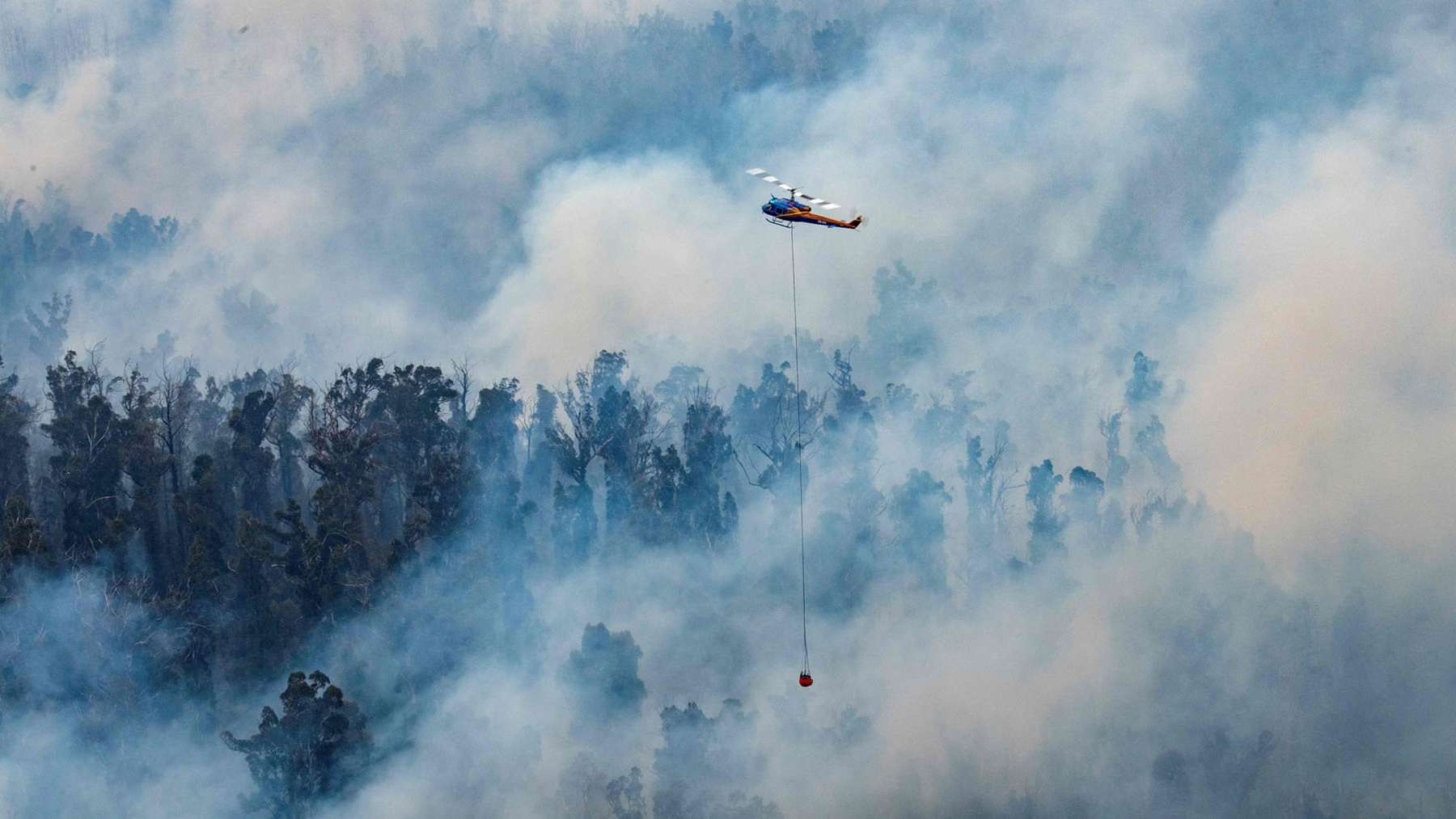 A helicopter dumps water on a fire in Victoria's East Gippsland region on Dec. 30, 2019. Fires continued to rage in Australia into 2020, causing fatalities and compromising air quality. (Photo courtesy of the Department of Environment, Land, Water and Planning)