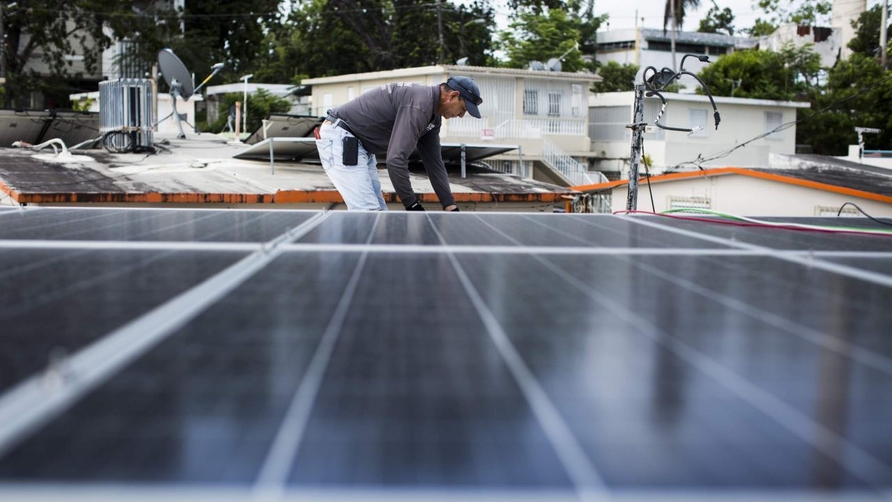 Luis Montalvo install a solar power system at Clínica Iella in San Juan, P.R., on July 5, 2018. Montalvo works with renewal power systems in the island and has seen more work after hurricane Maria struck in September of last year, and left the American territory in the dark. The clinic's new solar system, funded by Direct Relief, will help them maintain their medication if there's power interruption.  (Erika P. Rodriguez/Direct Relief)