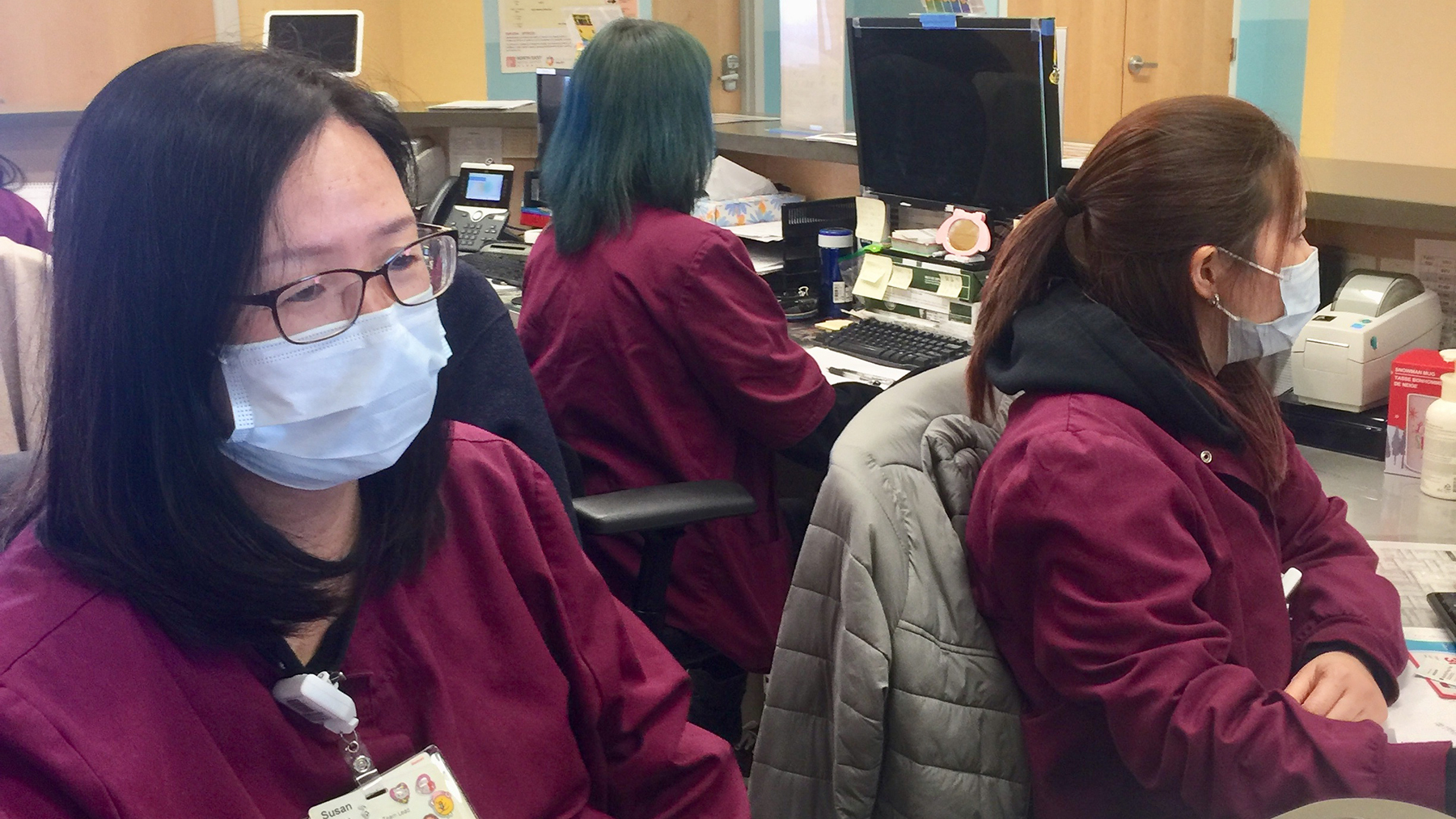 Front desk staff at North East Medical Services in the Bay Area wear masks as a protective measure during the coronavirus outbreak. (Photo courtesy of Dr. Kenneth Tai)