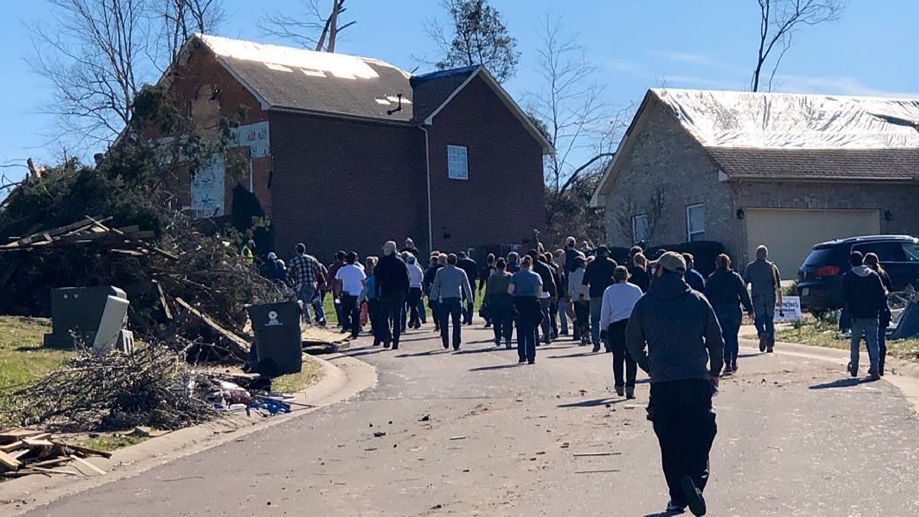 Volunteers walk past roadside damage in Mt. Juliet, Tennessee, after a March 3 tornado cut through the town. (Photo courtesy of Charis Health Center)