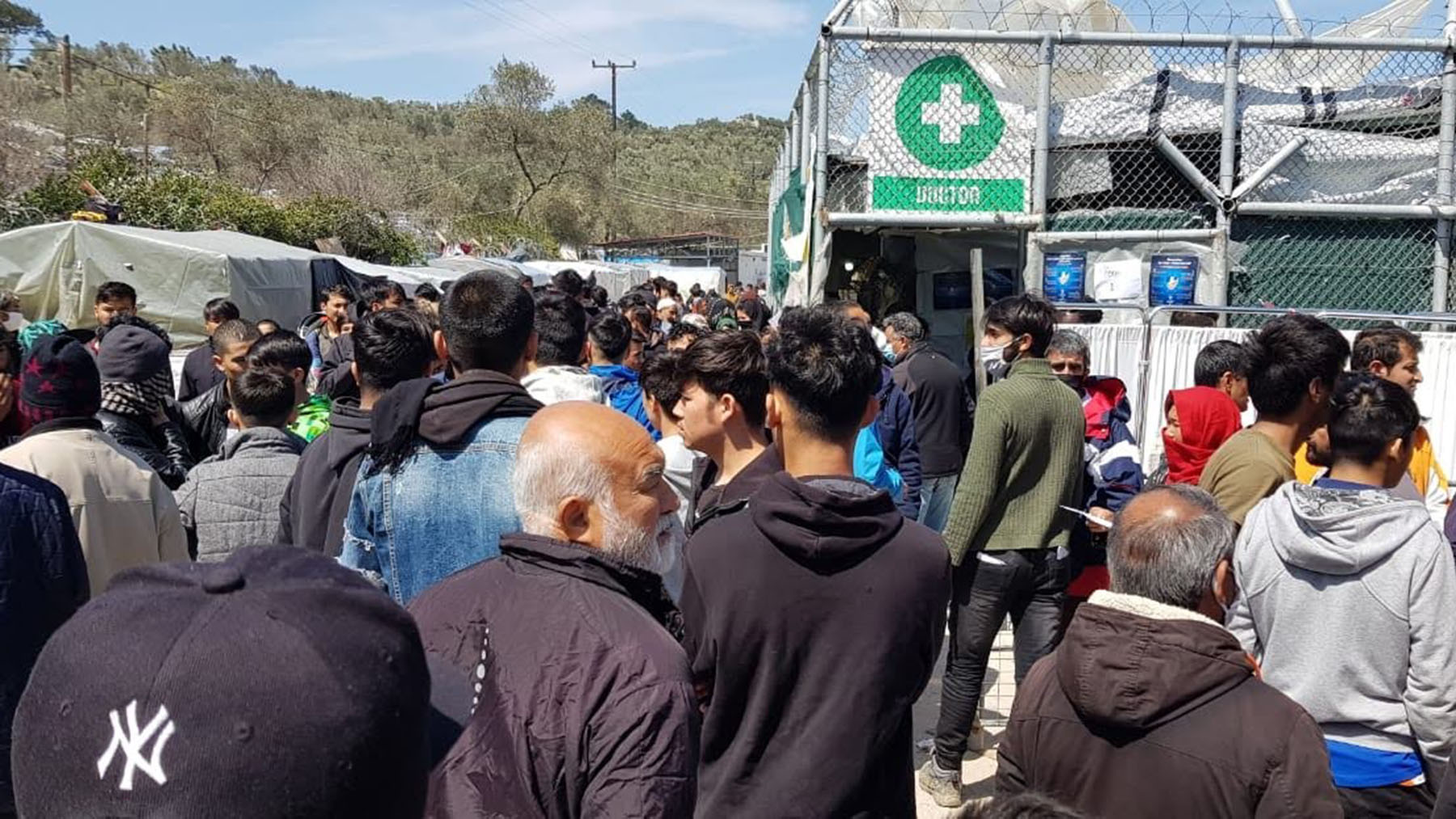 Residents of the Moria camp on the island of Lesbos. Residents of the camp frequently do not practice social distancing measures. (Photo courtesy of the Moria Coronavirus Awareness Team)