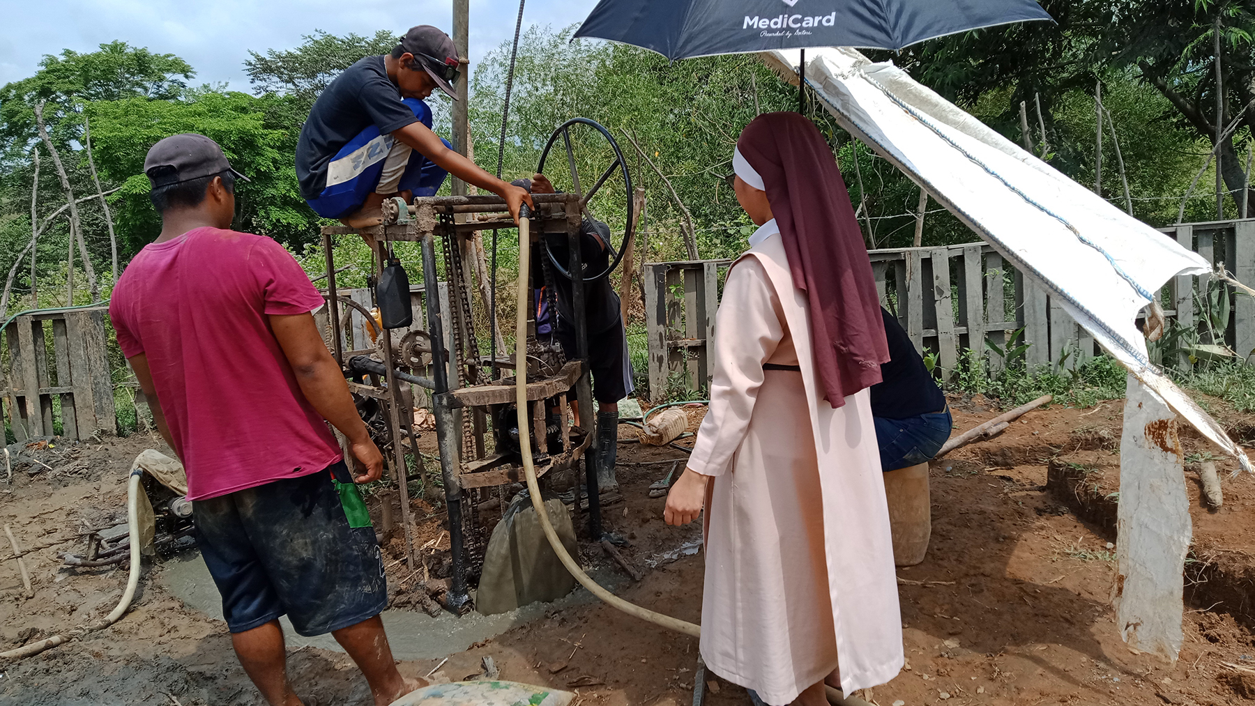 Community members watch a newly installed water pump at work. (Photo courtesy of FLDP GeEx Development Community Foundation)