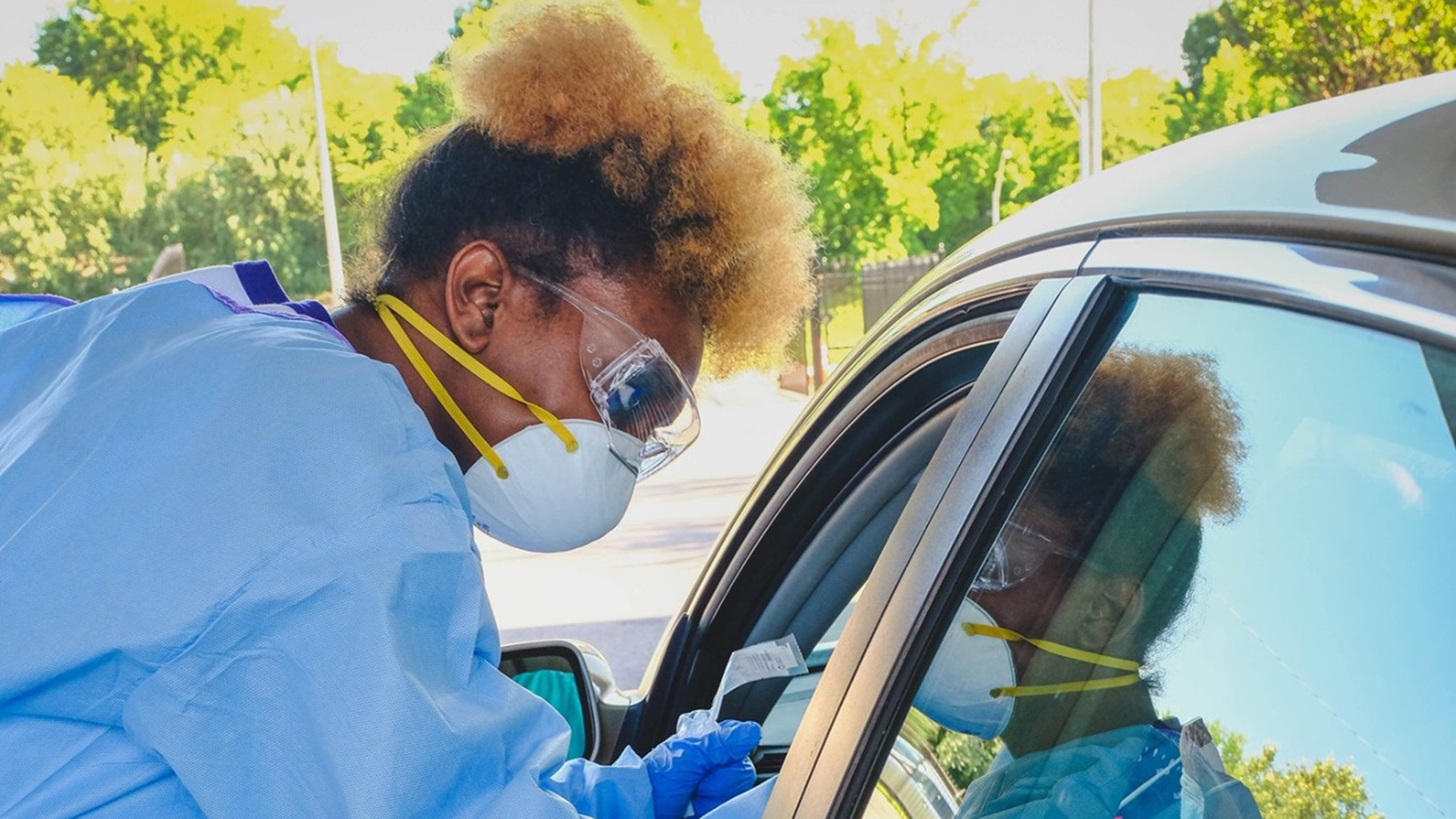 A Memphis health worker at a mobile testing site speaks to patients in a car. (Photo courtesy of Church Health)