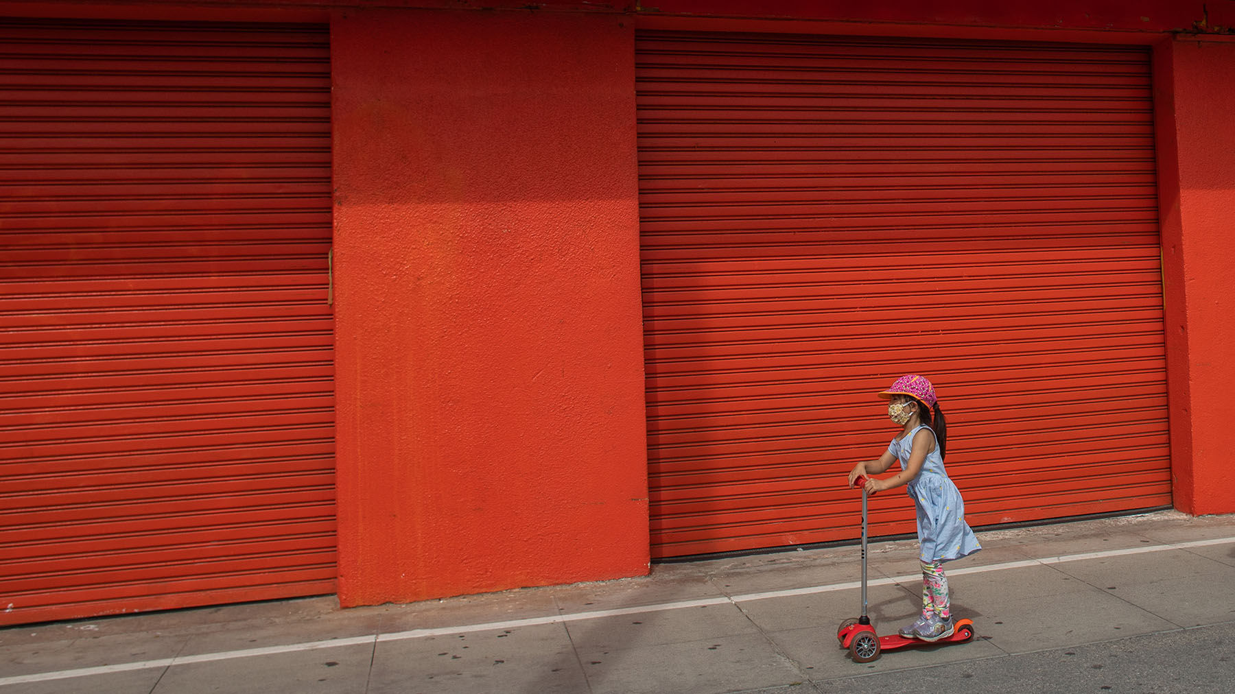 A young girl rides a scooter by the closed stores of the Boardwalk in Venice, California, during the coronavirus pandemic. Many mental health providers are working to reach children that have been impacted by school closures, including providers at health centers connected to nearby schools. (Photo by Apu Gomes/ AFP)