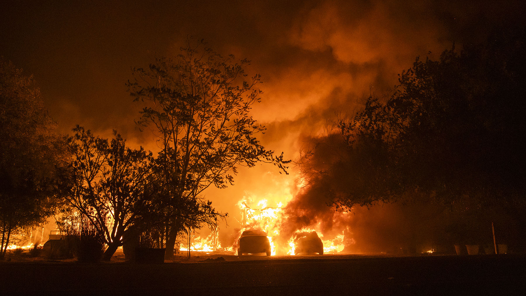 Vehicles catch fire in front of a burning home along Peaceful Glen Road during the Hennessy fire in Solano County, California, on Wednesday, Aug. 19, 2020. More Northern Californians were chased out of their homes by lightning-sparked wildfires that burned out of control in several counties amid a punishing heat wave that pushed temperatures into the triple digits. (Philip Pacheco/Bloomberg via Getty Images)