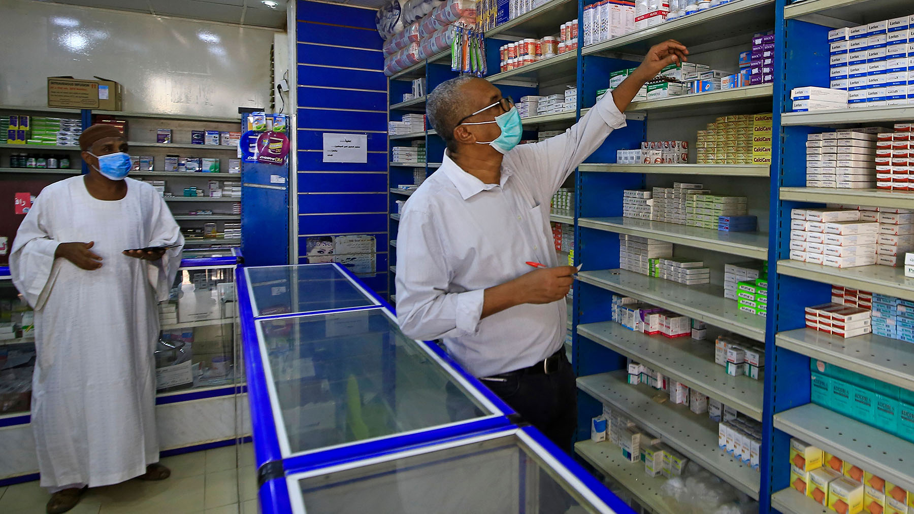Pharmacy owner Abdulaziz Othman, wearing a protective mask, serves a costumer at his drugstore in the Sudanese capital, Khartoum, on June 18, 2020, amid acute shortages of medicine as the country fights to control the spread of coronavirus. (Photo by Ashraf Shazly/AFP via Getty Images)