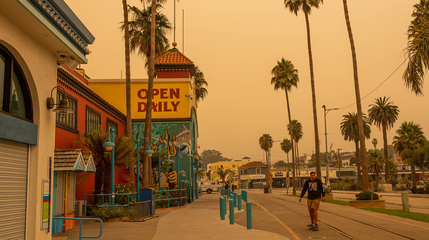 A young man skateboards in front of the boardwalk in Santa Cruz, California, on Aug. 20, 2020, as smoke from the CZU August Lightning Complex fires filled area skies. (Anna Maria Barry-Jester/KHN)