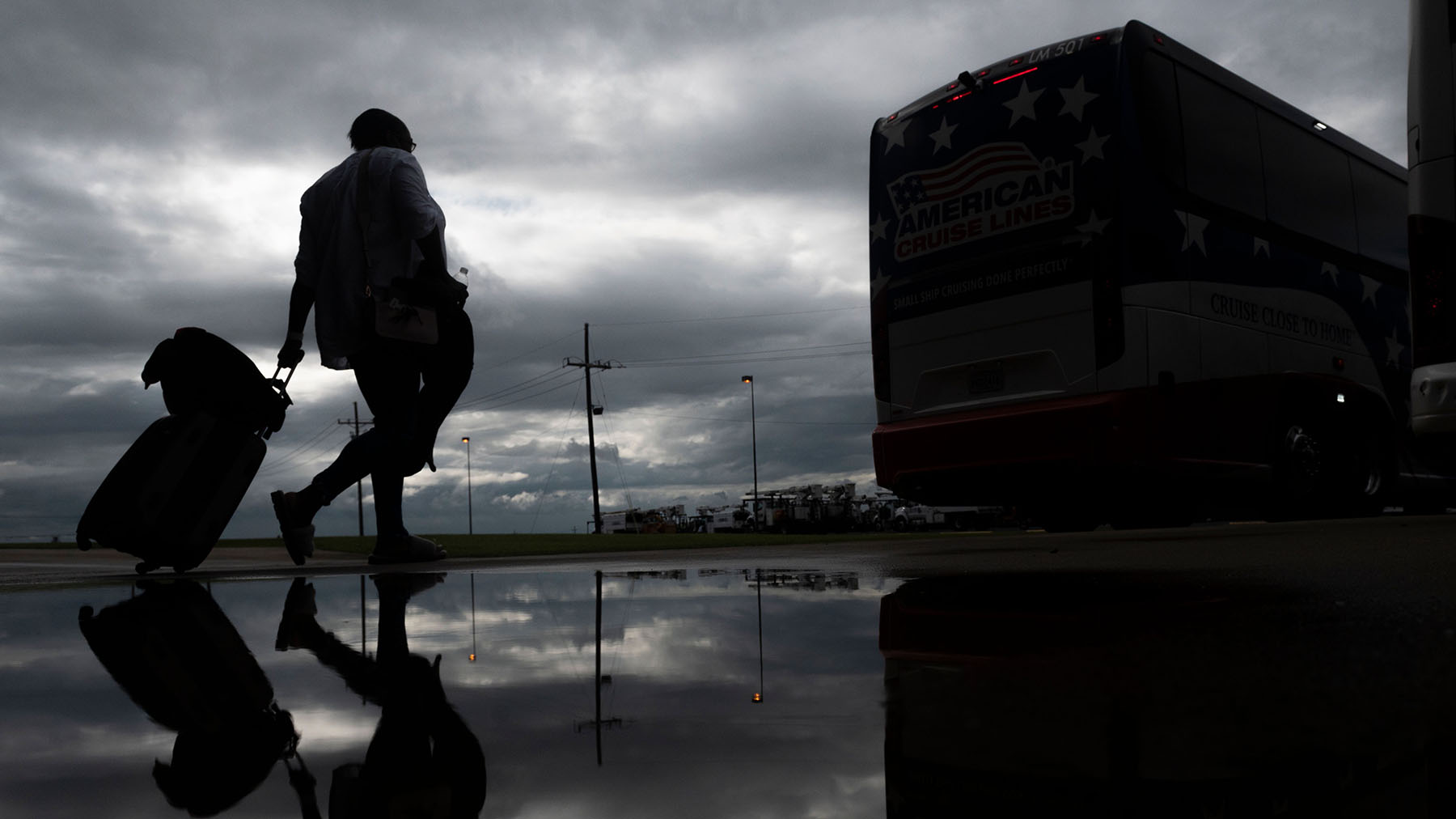 A woman rolls a suitcase as she walks to board a bus for evacuation before the arrival of Hurricane Laura in Lake Charles, Louisiana, on August 25, 2020, amid the coronavirus pandemic.  (Photo by Andrew Caballero-Reynolds/AFP)