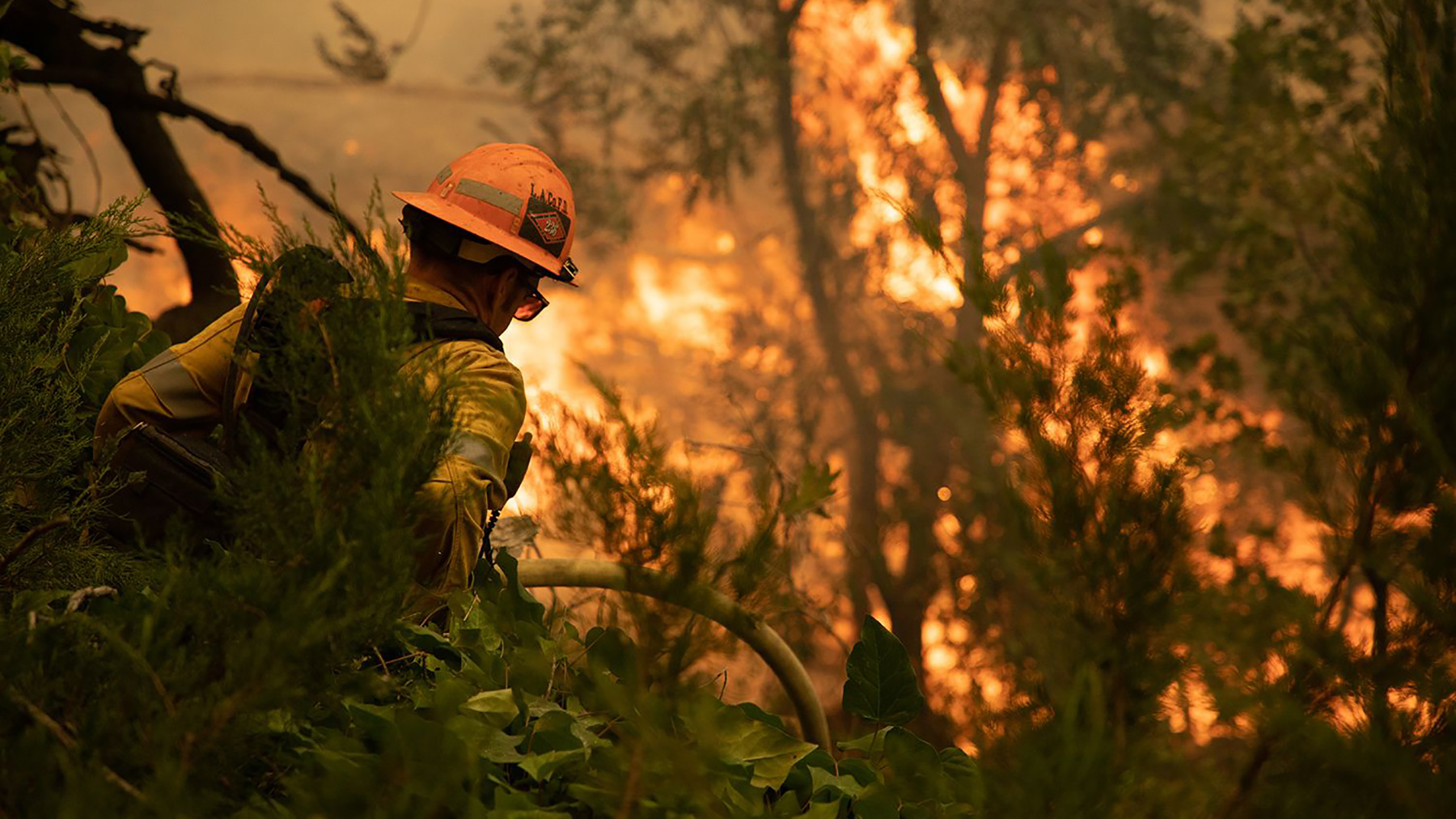 A firefighter works to quell the flames of the El Dorado Fire burning in California's San Bernardino mountains on Sept. 10, 2020. Fires are burning across a dozen U.S. states, creating health challenges for residents while the pandemic stretches on. (Photo courtesy of San Bernardino County Fire Department)