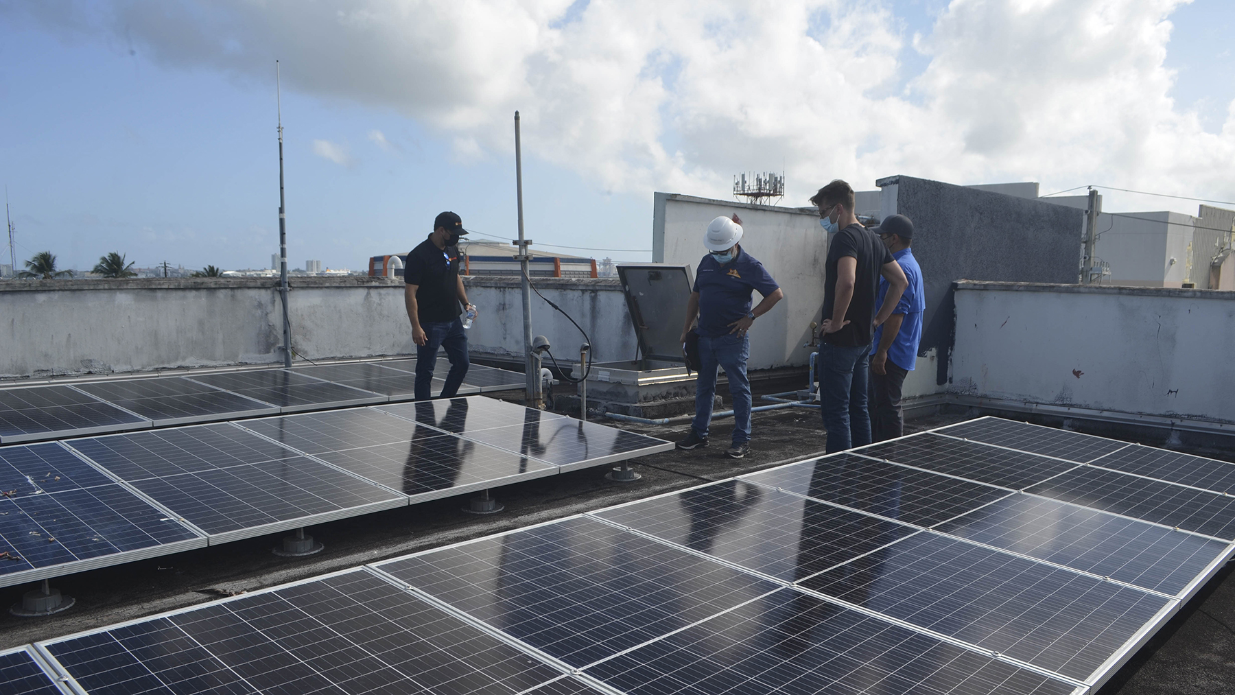 Firefighters at the Cataño fire station in Puerto Rico and a Direct Relief staff member examine solar panels newly installed on the station roof. (Ana Umpierre/Direct Relief)