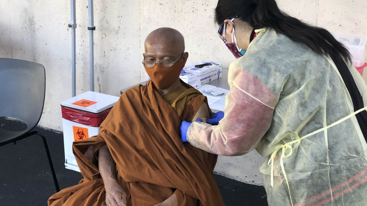 A Thai monk receives a vaccination from Kheir Center staff as part of the health center's outreach to specific patient populations. (Photo courtesy of Kheir Center)