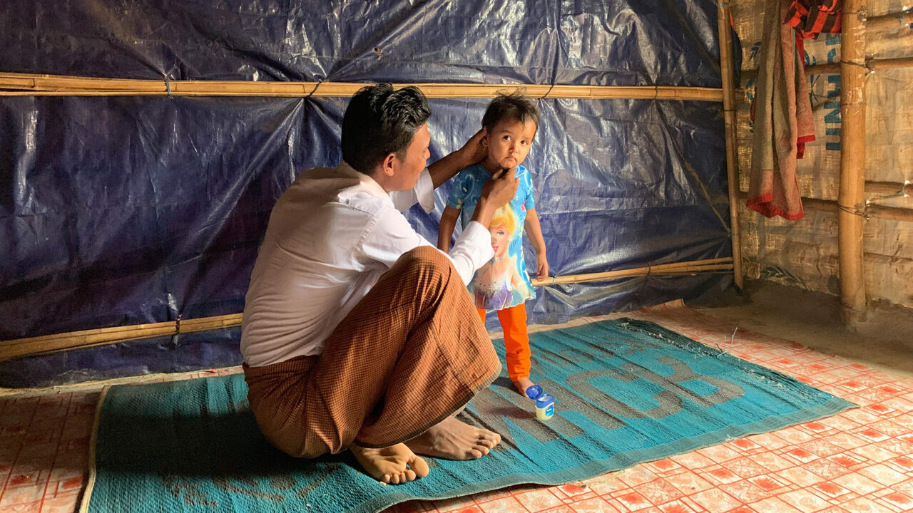 A father tends to his child's skin in Cox's Bazar, Bangladesh. As part of the Vaseline Healing Project, medical missions were conducted at HOPE's field hospital in Cox's Bazar, Bangladesh to bring dermatological care to Rohingya refugees without access. (Ellen Cho/Direct Relief)