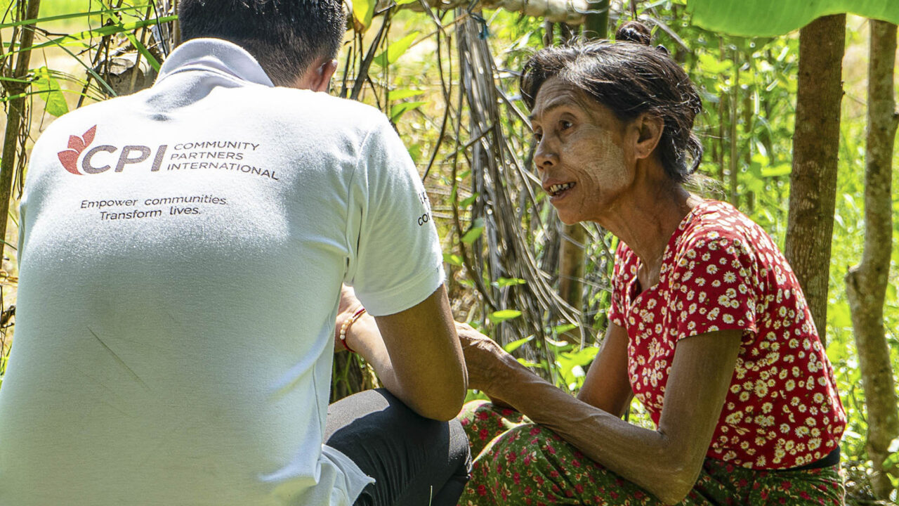 A Community Partners International staff member speaks with a community member in the Ayeyarwady Region of Myanmar. (Photo by Gregg Butensky/Kirana Productions for Community Partners International)