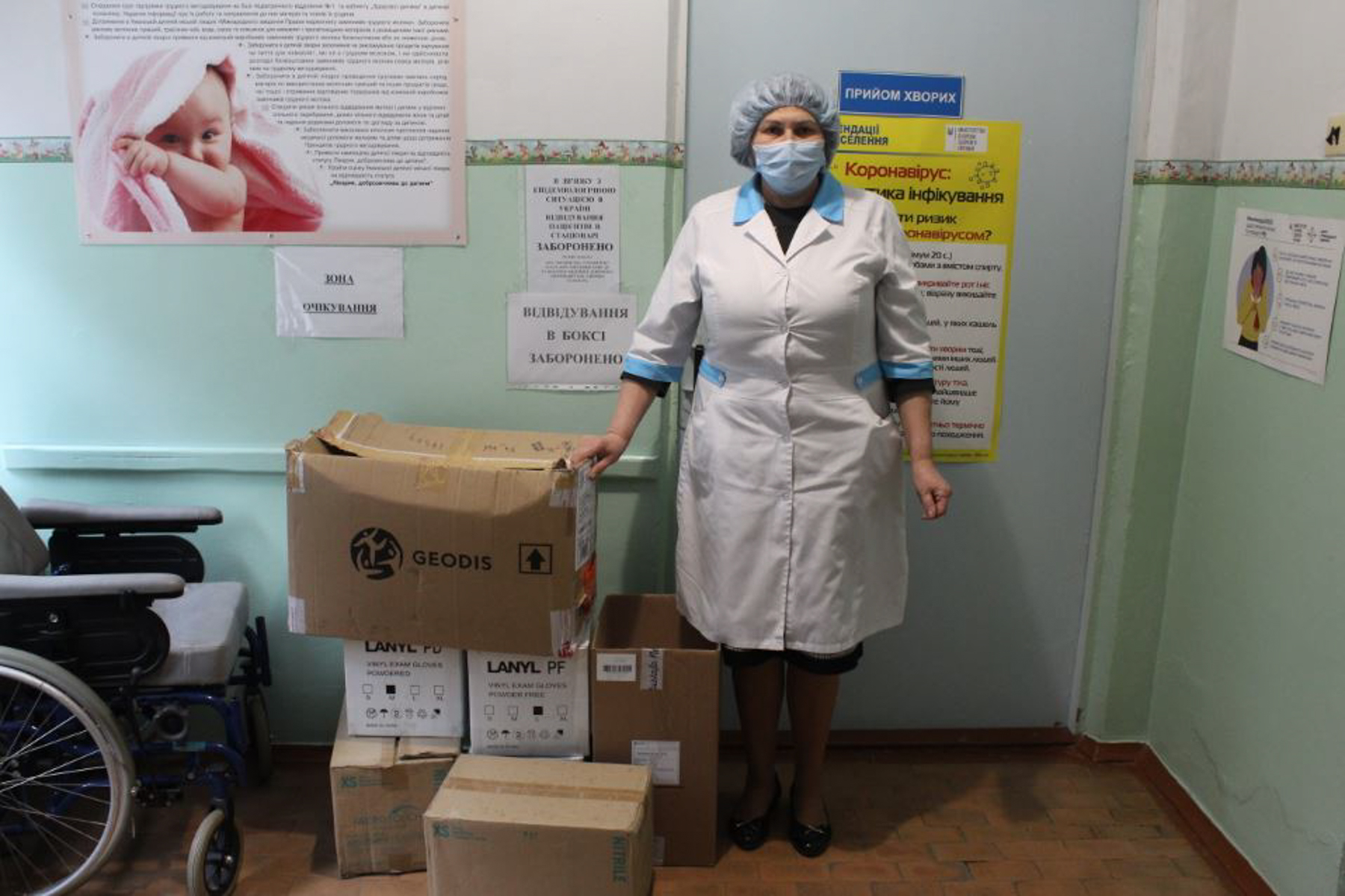 A nurse of the children's hospital in front of the patient reception room. The boxes contain donated disposable gloves, and medical supplies. (Photo courtesy of Charity Fund Modern Village and Town)