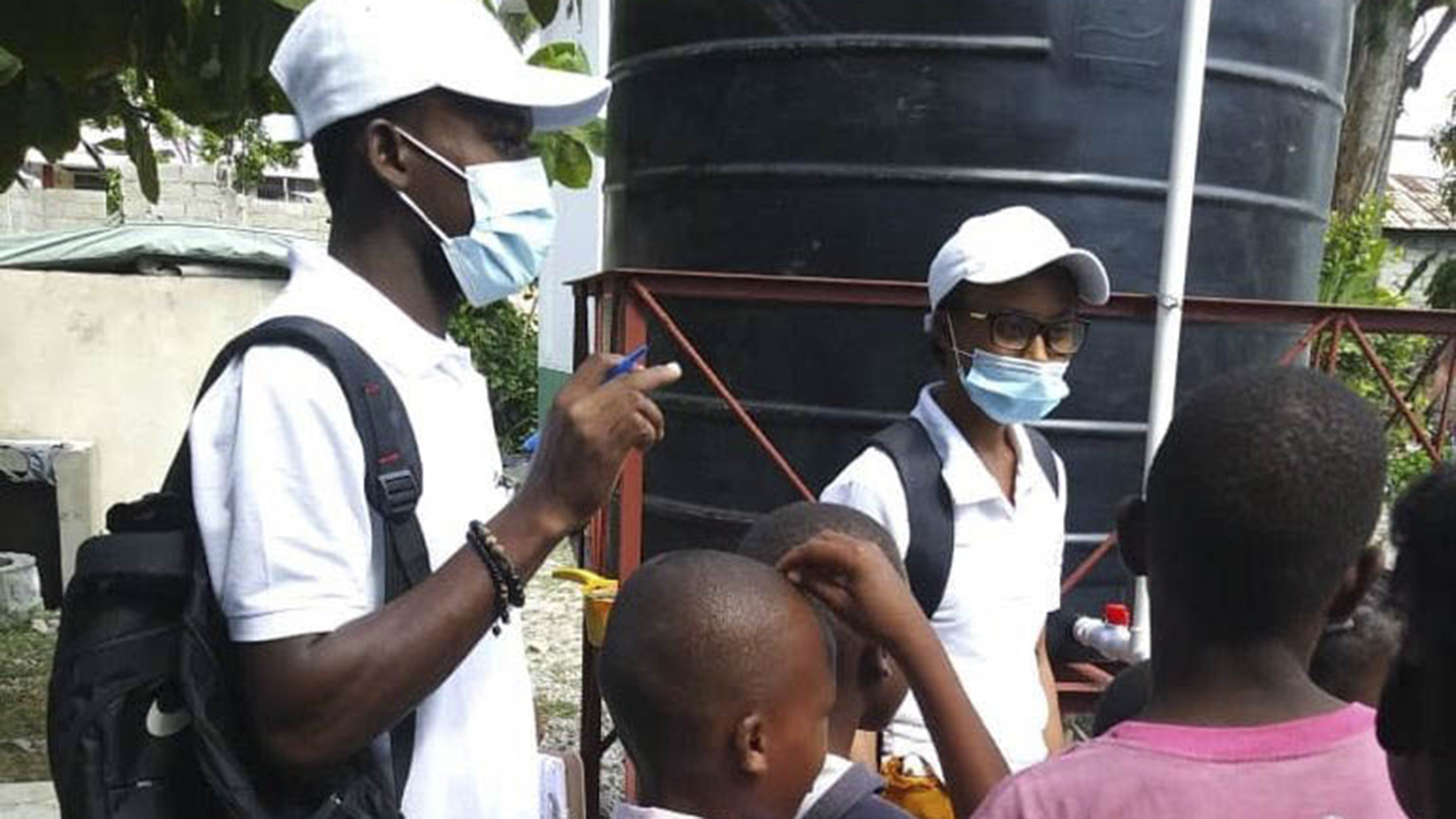 GHESKIO staff work with children in a displacement camp. (Photo courtesy of GHESKIO)
