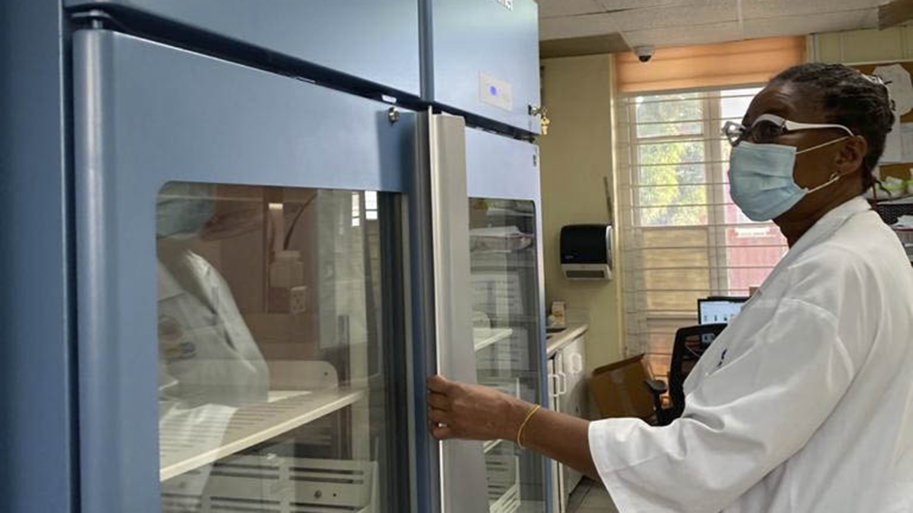 A pharmacist with one of the medical grade refrigerators provided by Direct Relief. (Photo courtesy of the National Health Fund)