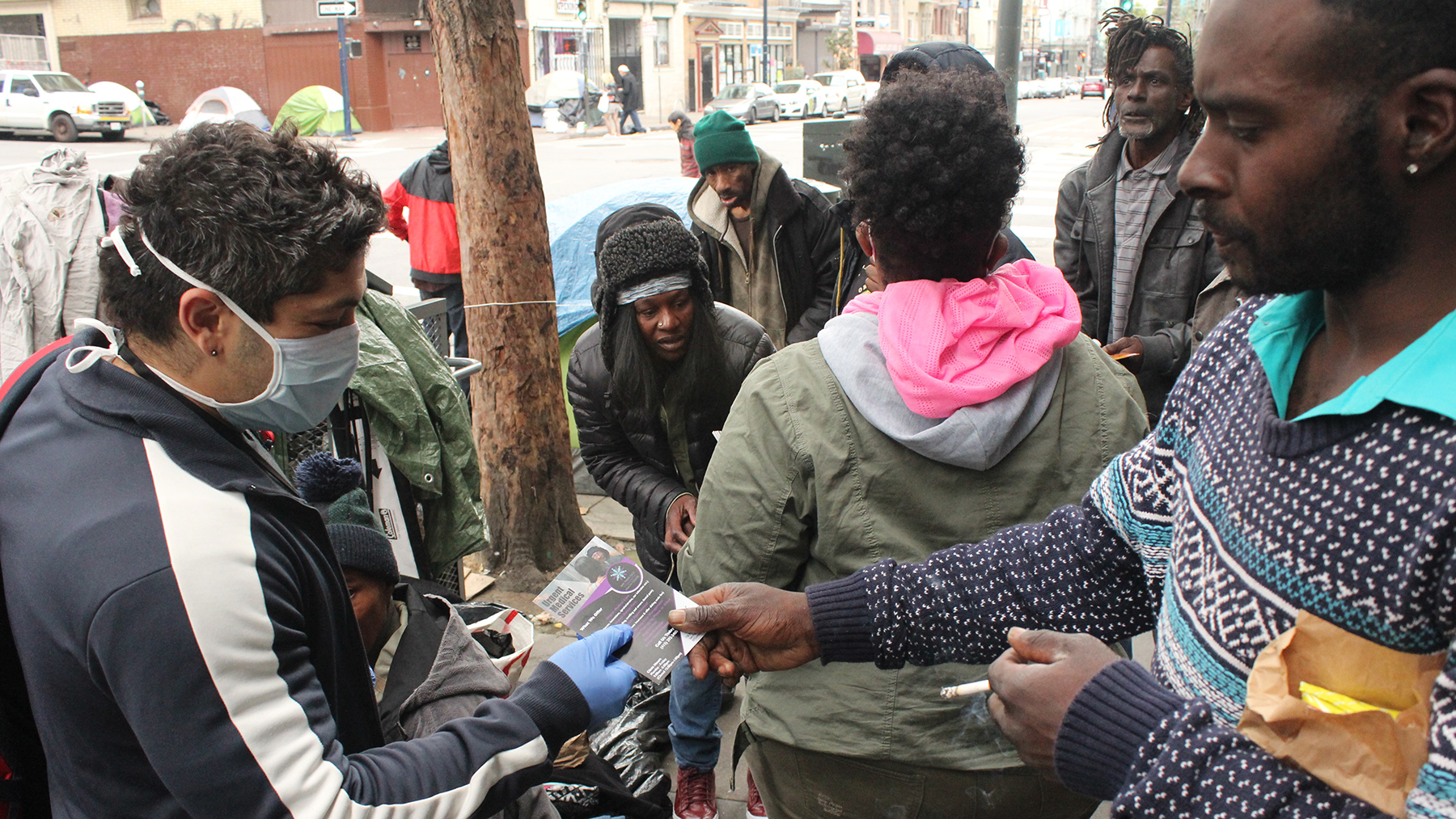 A San Francisco Community Health Center staff member distributes pamphlets to people in San Francisco's Tenderloin district. (Photo courtesy of San Francisco Community Health Center)