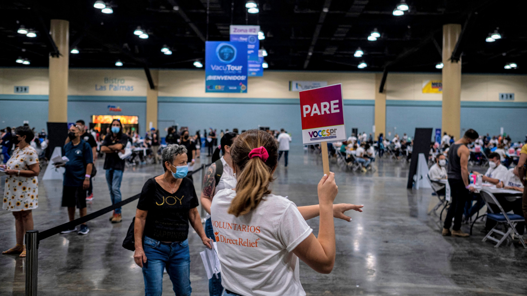 A Direct Relief volunteer assists people inside the Puerto Rico Convention Center during the first mass Covid-19 vaccination event in San Juan, Puerto Rico on March 31, 2021. (Photo by Ricardo ARDUENGO / AFP)