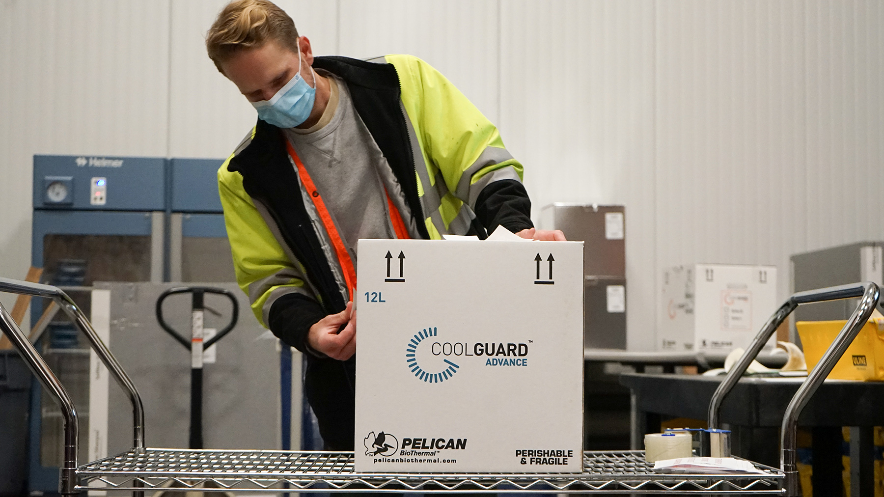 Temperature-sensitive medications bound for India are packed into cold shippers in one of Direct Relief's cold rooms at the organization's distribution facility in Santa Barbara, California.. (Lara Cooper/Direct Relief)