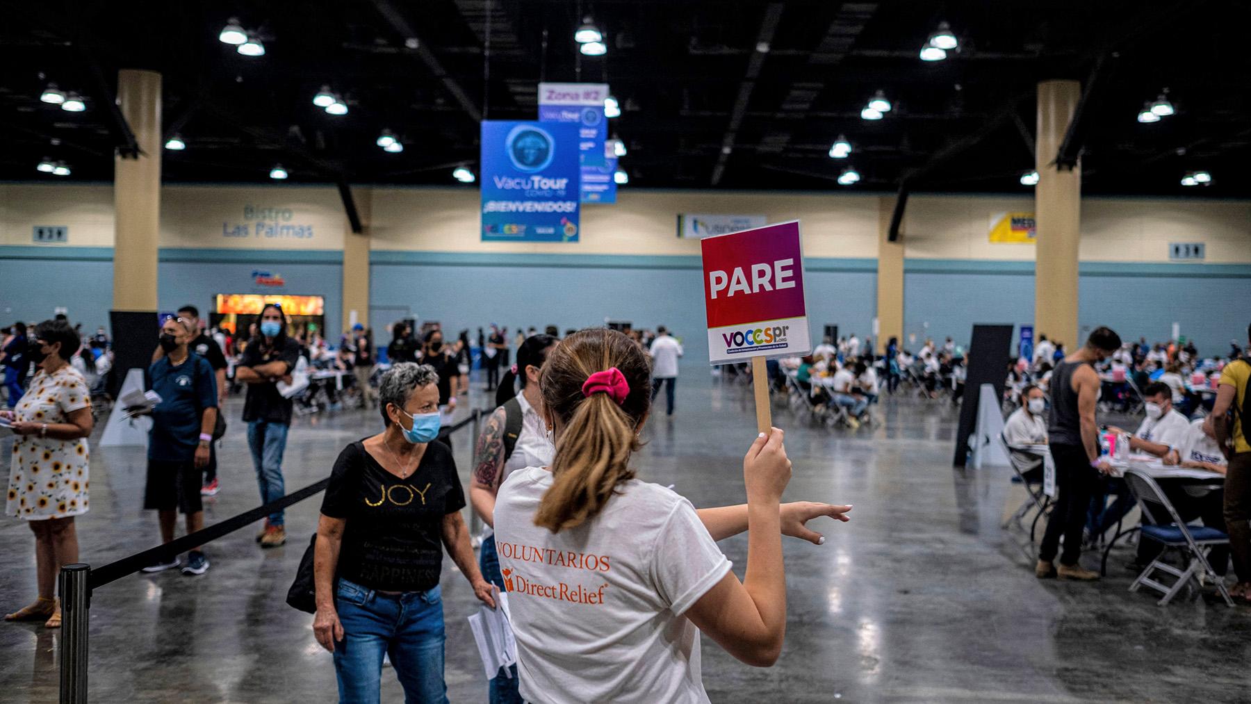 Un voluntario de Direct Relief ayuda a las personas dentro del Centro de Convenciones de Puerto Rico durante el primer evento masivo de vacunación Covid-19 en San Juan, Puerto Rico el 31 de marzo de 2021. (Foto de Ricardo ARDUENGO / AFP)