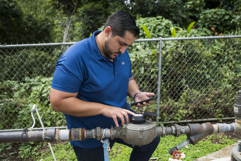 Rodríguez verifica la presión del agua en un sistema de bomba de agua comunitaria instalado recientemente en Yabucoa, Puerto Rico. (Foto de Dennis M. Rivera Pichardo para Direct Relief)