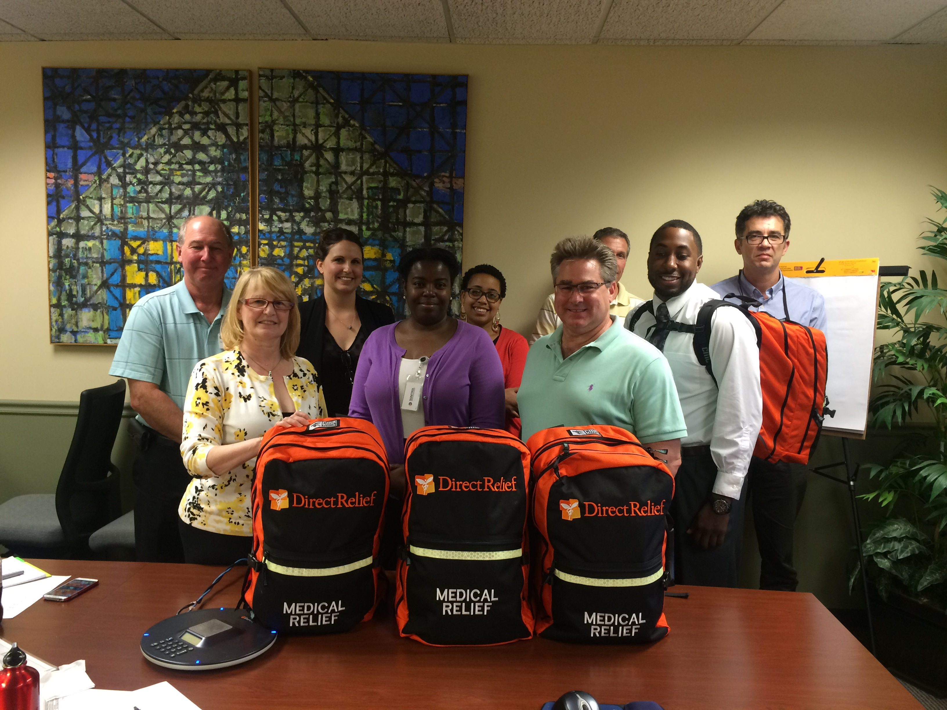 Community Health Center Association of Connecticut staff and health center representatives smile with the Direct Relief Medical Packs. Each of Connecticut's 16 health centers will receive a backpack.
