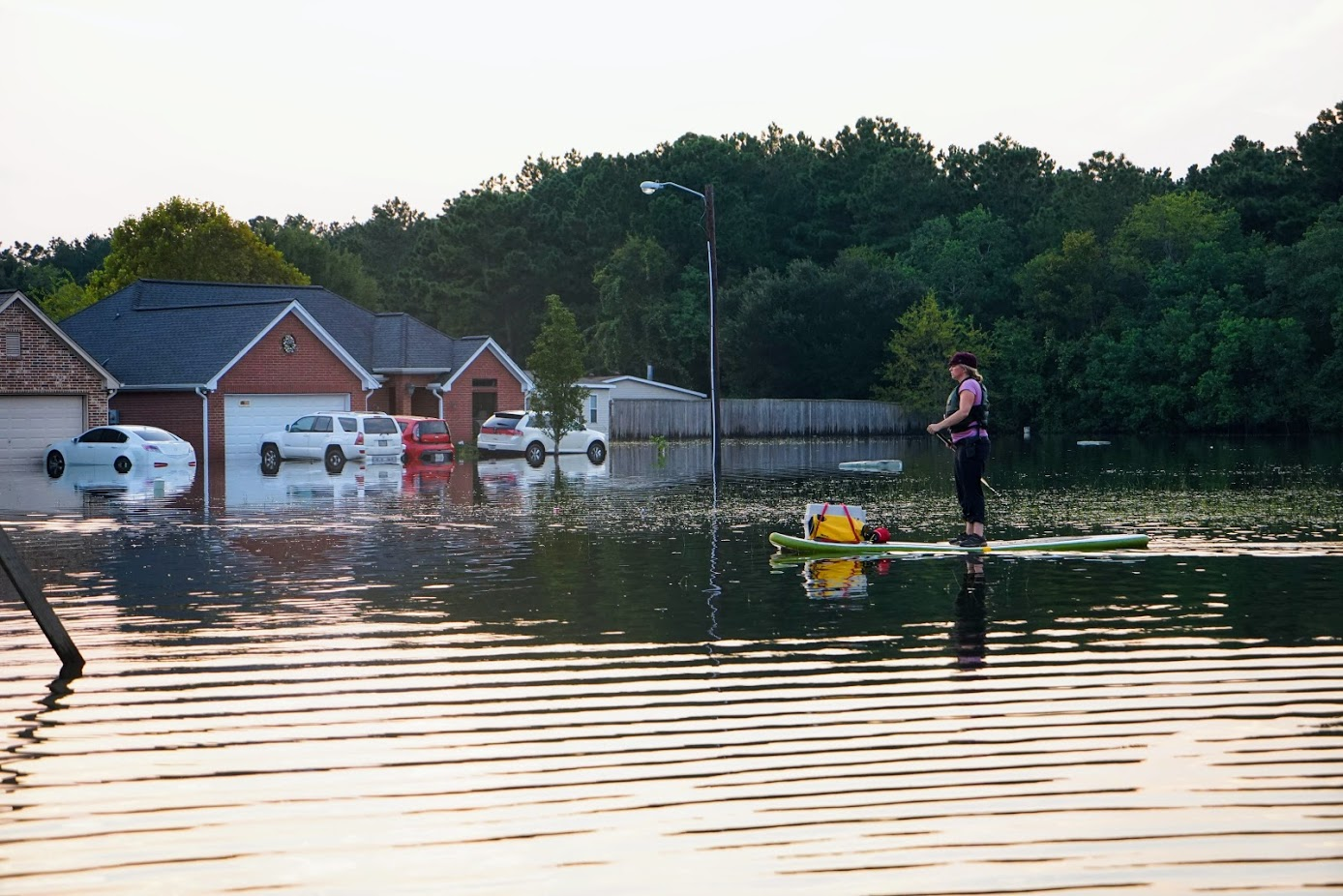 A woman paddles through subdivision covered by the floodwaters near Beaumont, Texas. (Lara Cooper/Direct Relief photo)