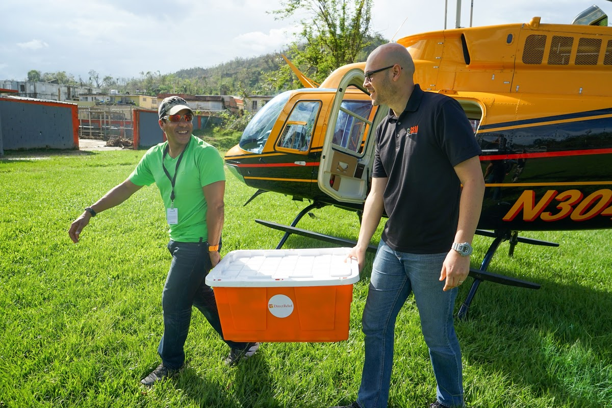 Daniel Ramos of the Puerto Rico Primary Care Association and Alexis Romero of the Corporacion de Servicios Medicos, a clinic in Utuado, unload medicines from a helicopter, provided by Samaritan's Purse. (Lara Cooper/Direct Relief)