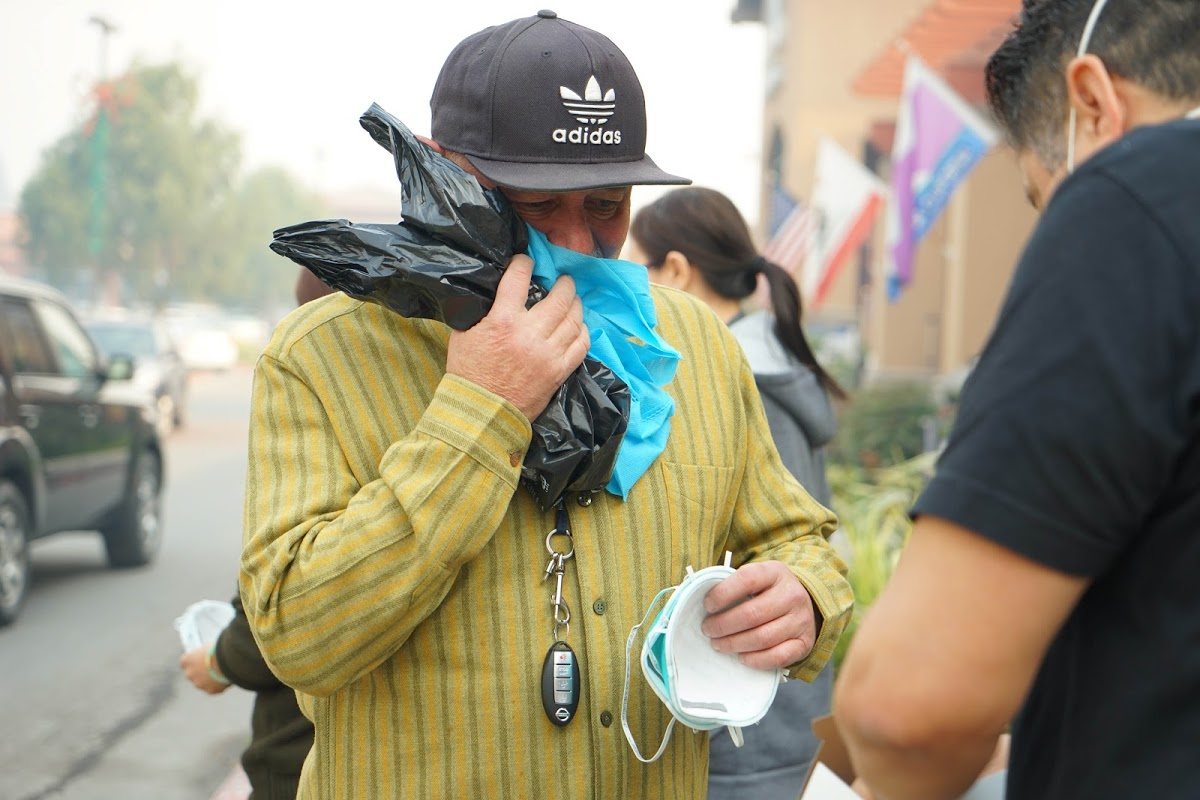 A resident of Carpinteria, California, picks up an N-95 mask during the Thomas Fire in December, 2017. Air quality is often compromised during wildfires, and Direct Relief shipped masks Tuesday to first responders in Lake County, where the Pawnee Fire is burning. (Lara Cooper/Direct Relief)