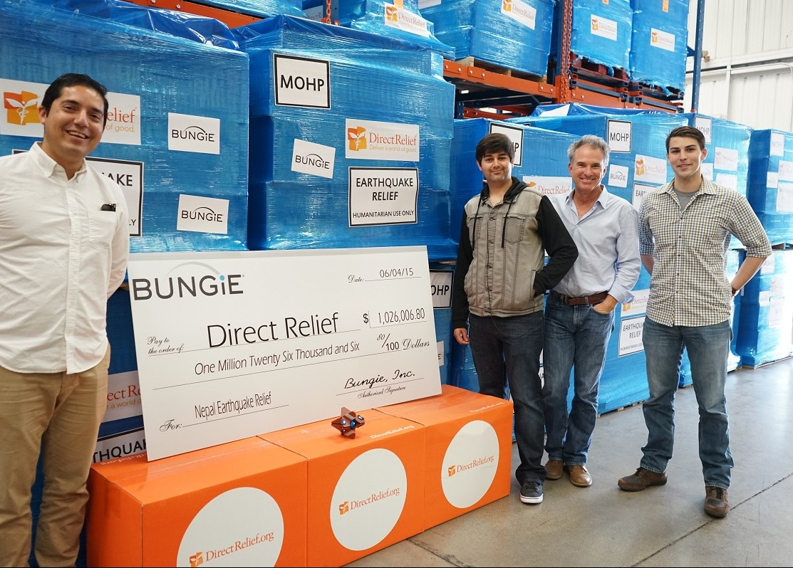 (From left to right) Santa Barbara-based Bungie gamers, Eddie Moreno, Raul Aguirre, and Ian Clark present the check for more than $1 million to Direct Relief CEO Thomas Tighe (second from right) to support the organziation's Nepal earthquake response efforts.