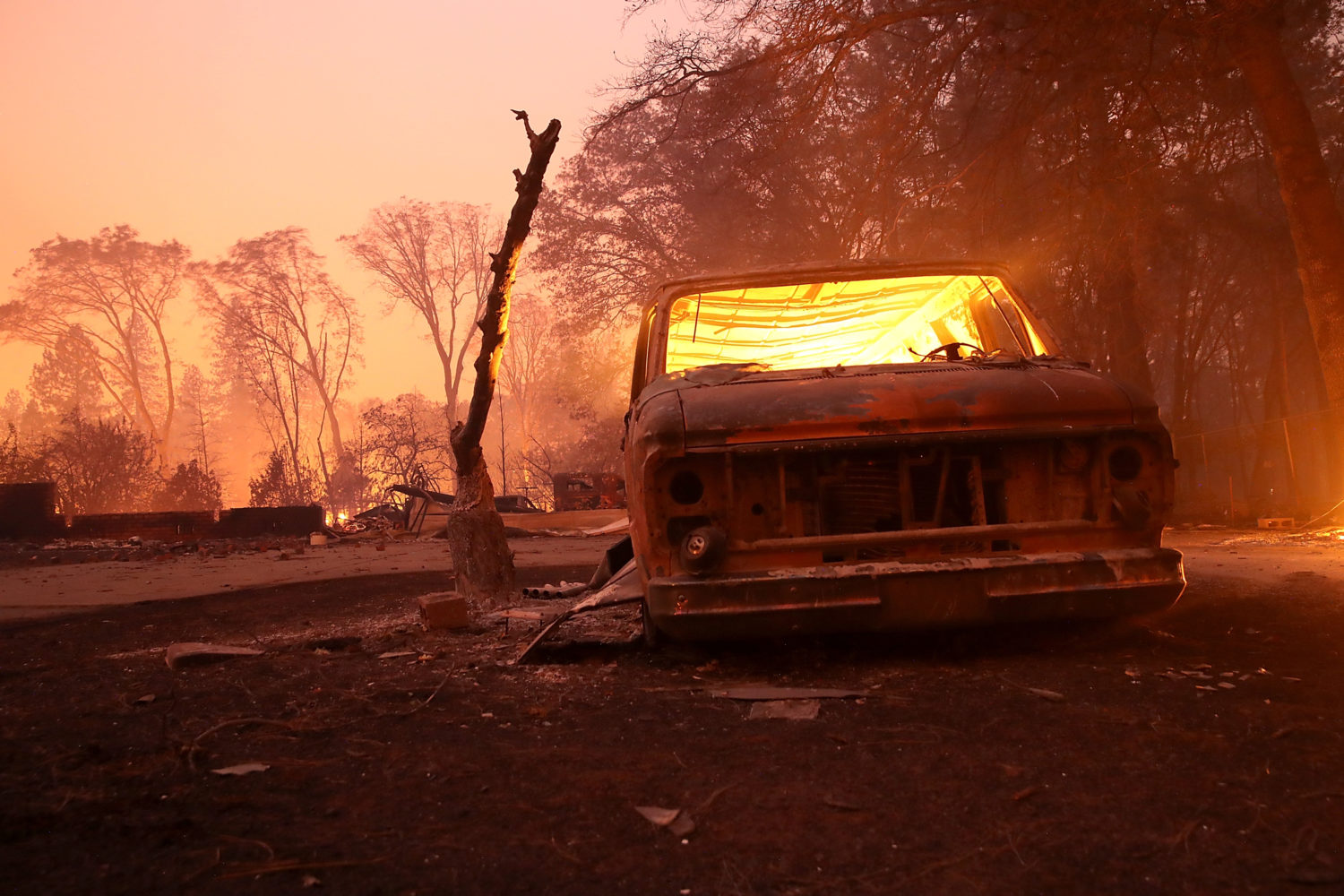 A burned-out van smolders after the Camp Fire moved through Paradise, California on Nov 8, 2018. (Photo by Justin Sullivan/Getty Images)